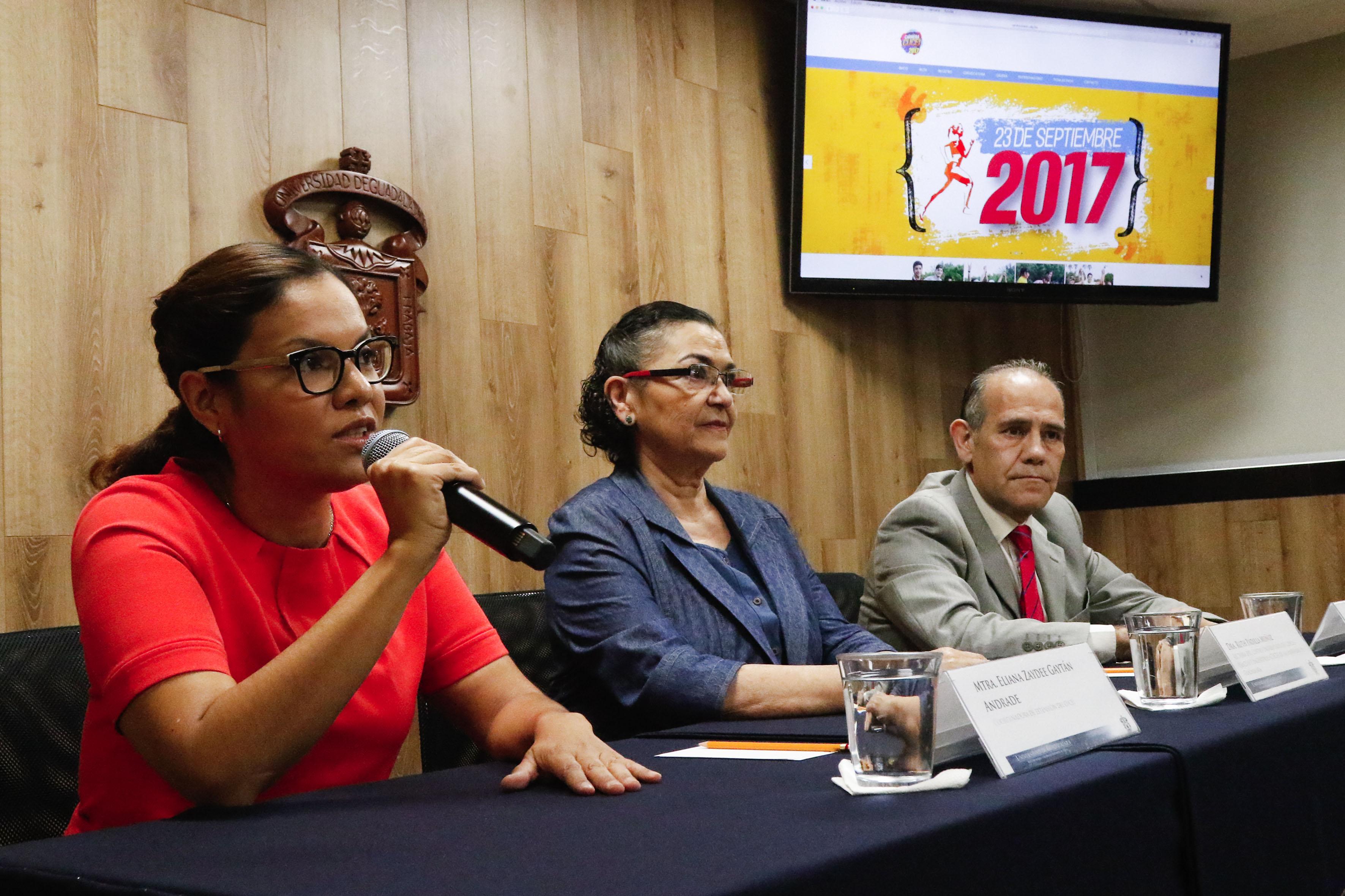Maestra Eliana Gaytán Andrade, coordinadora de Extensión del CUCEI, con micrófono en mano haciendo el uso de la palabra en rueda de prensa.