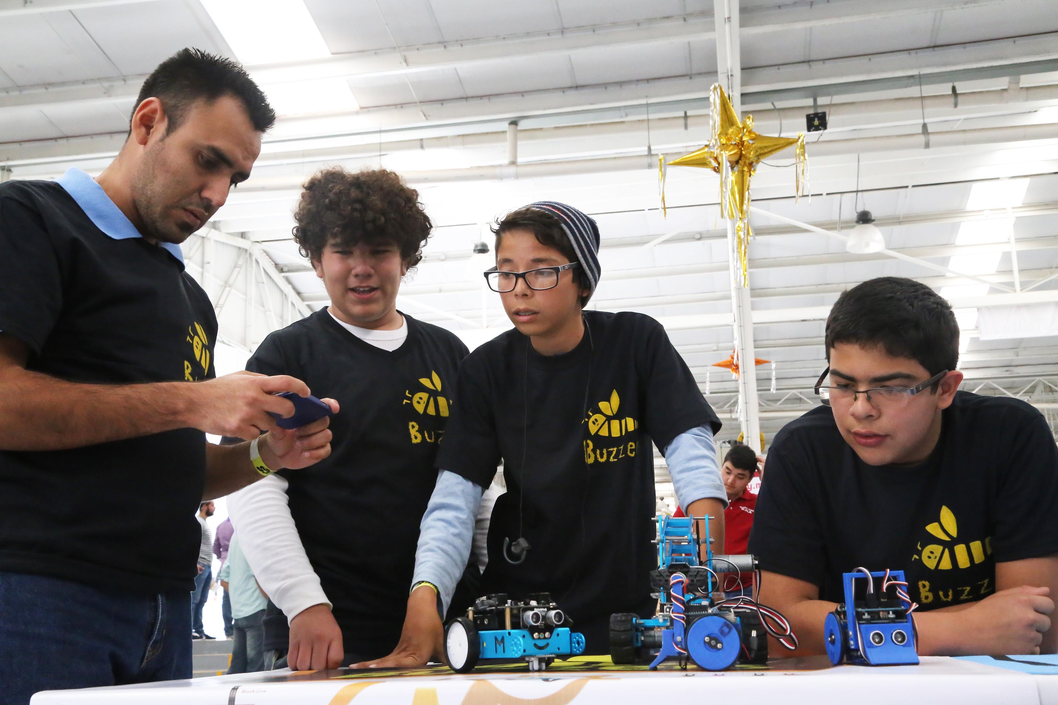 Equipo de estudiantes con su respectivos drones, tratando de impulsarlos con un dispositivo de control remoto.