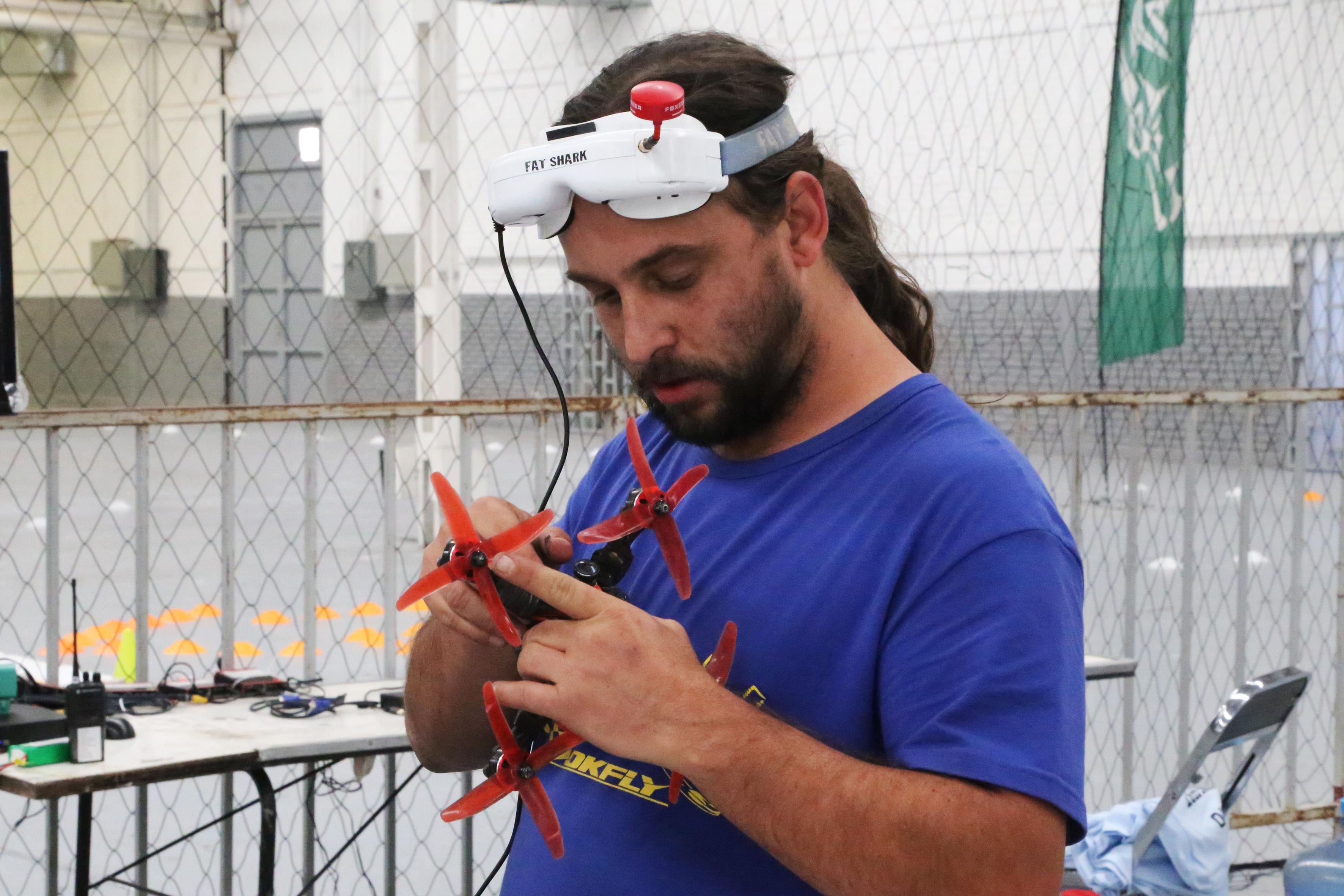 Persona masculina, dentro de un laboratorio y área equipada para prueba de vuelo de drones; sujetando a su drone para equiparlo y ajustar su cámara.
