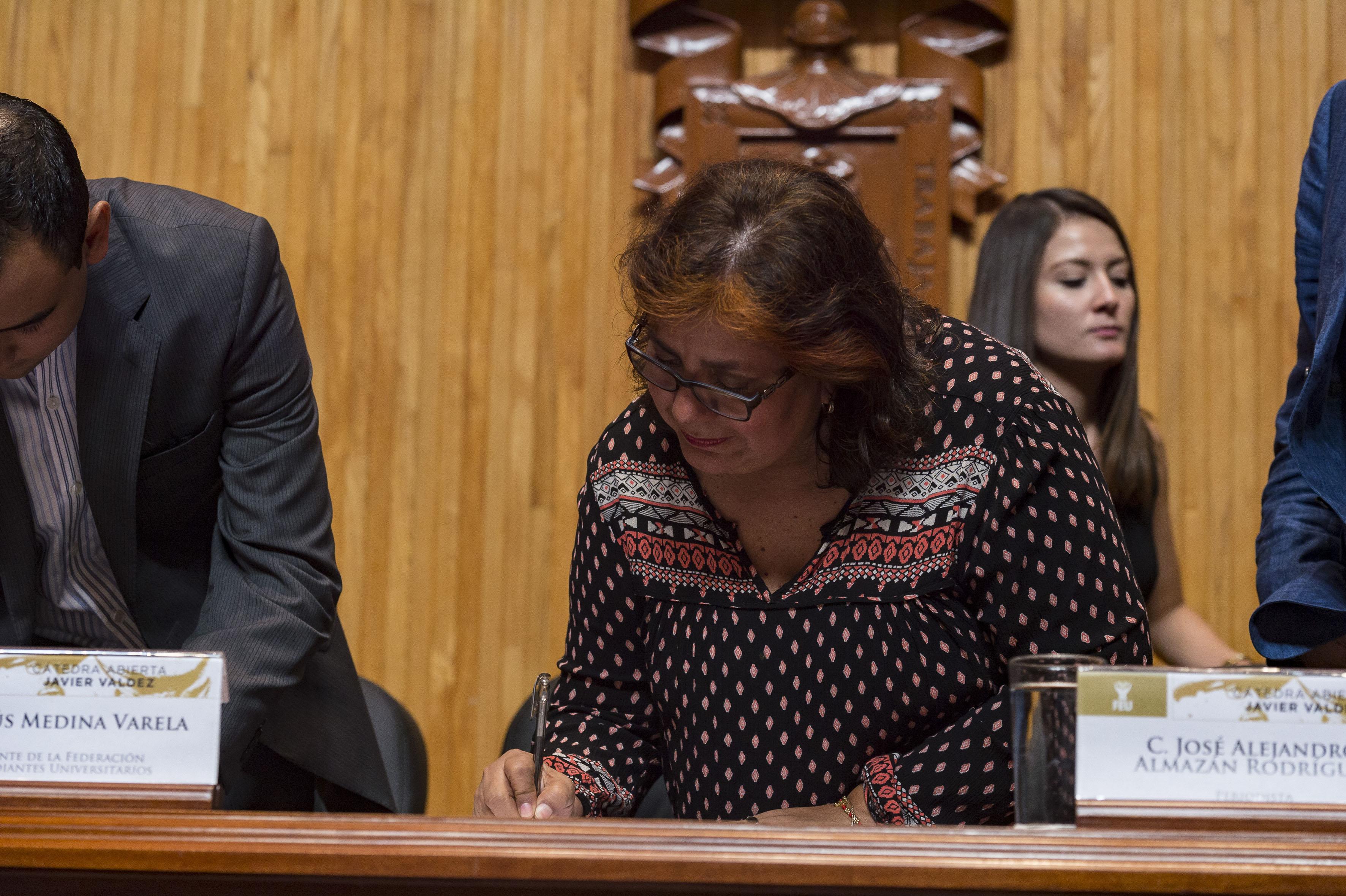 Griselda Inés Triana López, esposa de Valdez firmando  la carta de intención de la cátedra, recibió un dibujo del periodista realizado por Daniel Castellanos Carrillo, egresado del Centro Universitario de Arte, Arquitectura y Diseño (CUAAD).