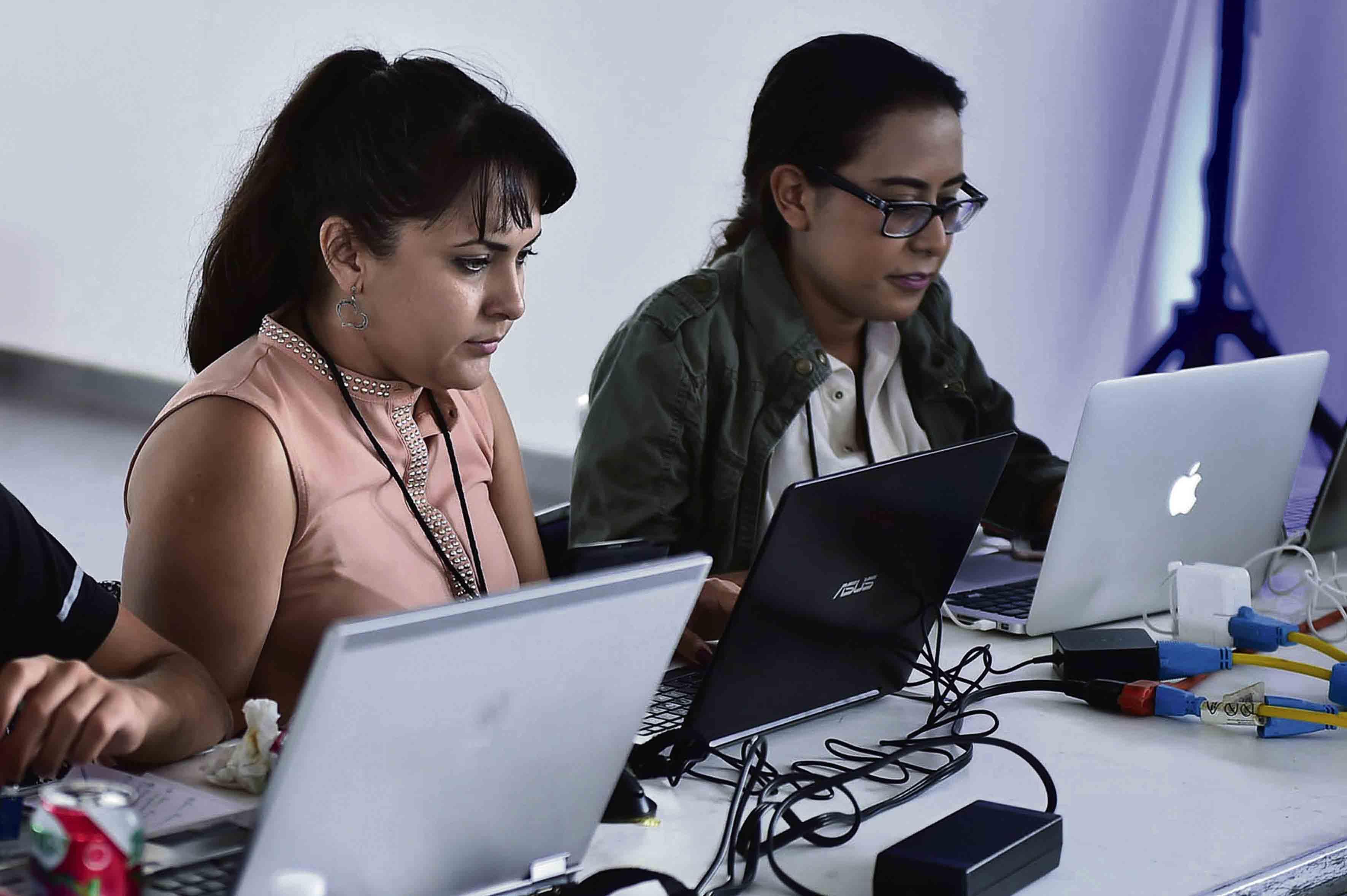 Mujeres estudiantes, haciendo uso de equipos de cómputo.