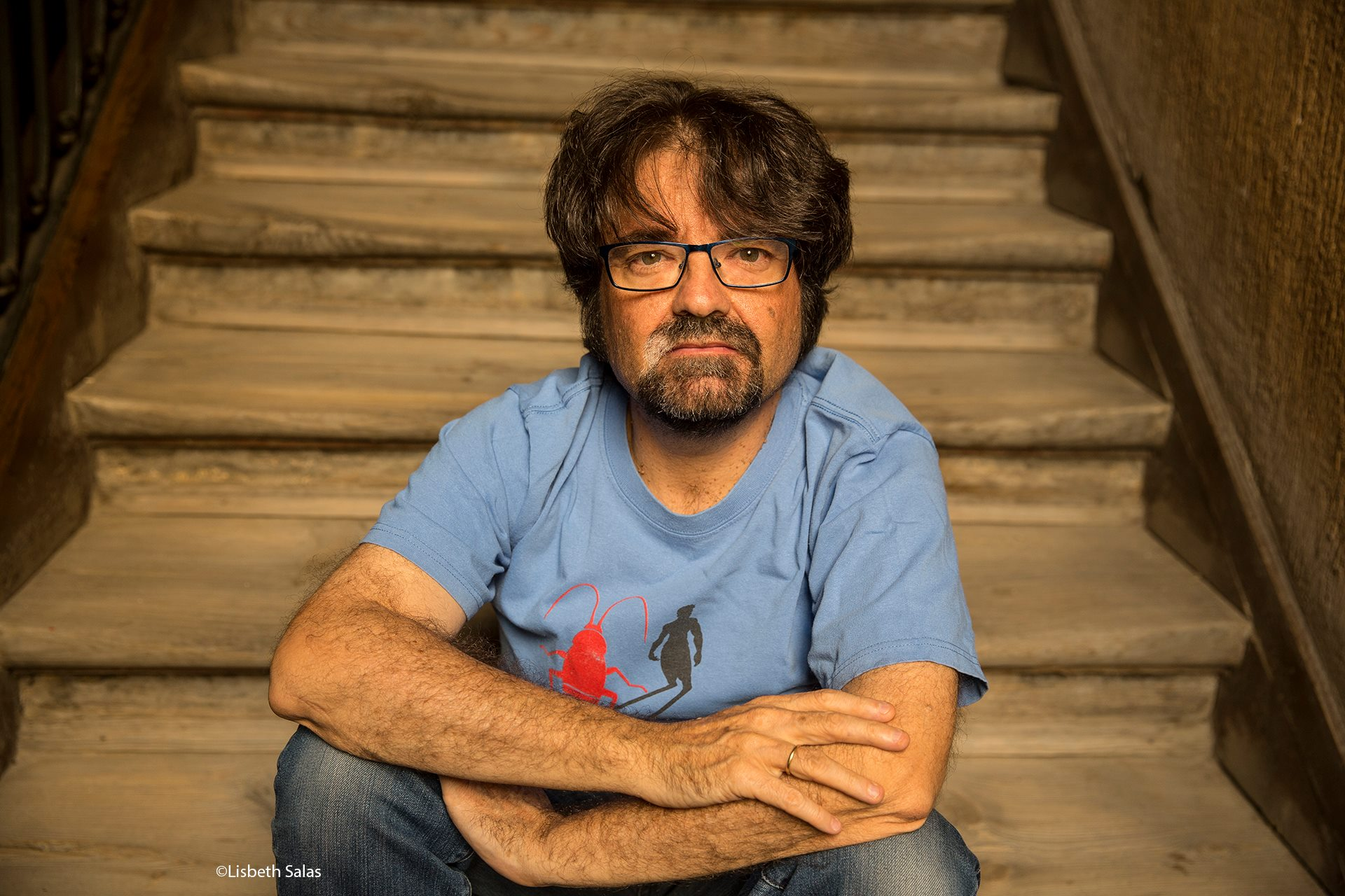 Juan Casamayor, editor madrileño y fundador de Páginas de Espuma. Sentado en las escaleras de madera de algún recinto.
