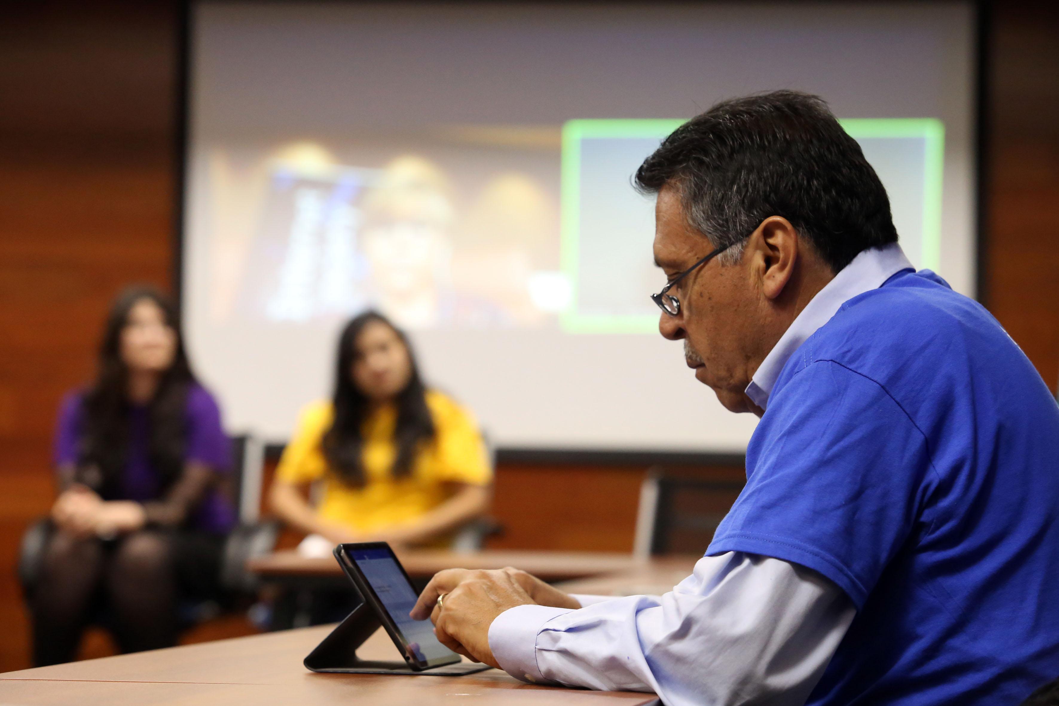 Hombre adulto haciendo uso de tableta digital, participando en el panel de discusión de la internet society.