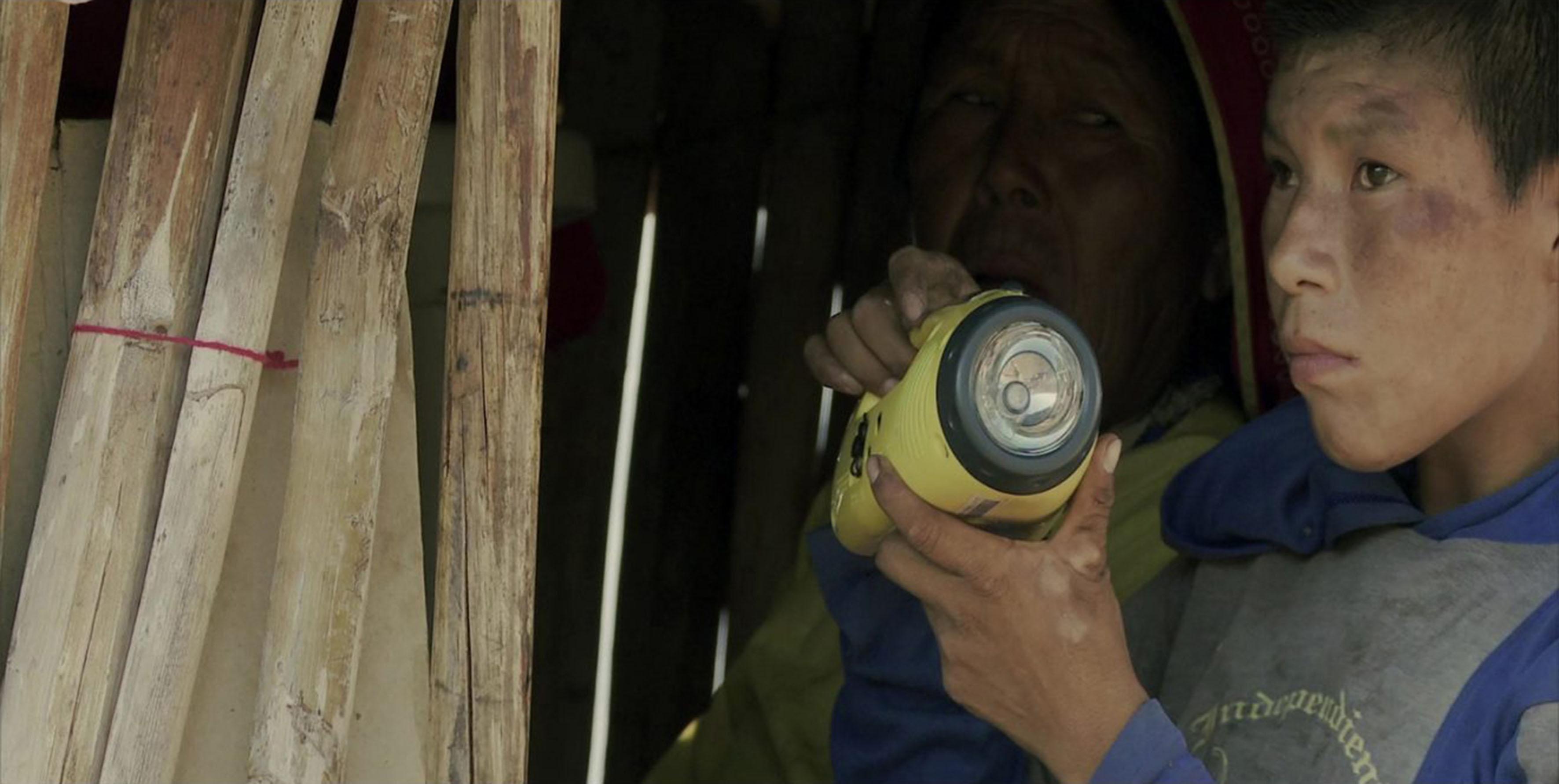 Abuela y niño Wixárica, cargando una lámpara, mientras se encuentra dentro de una pequeña choza hecha de pequeños troncos de árbol de madera y cartón.