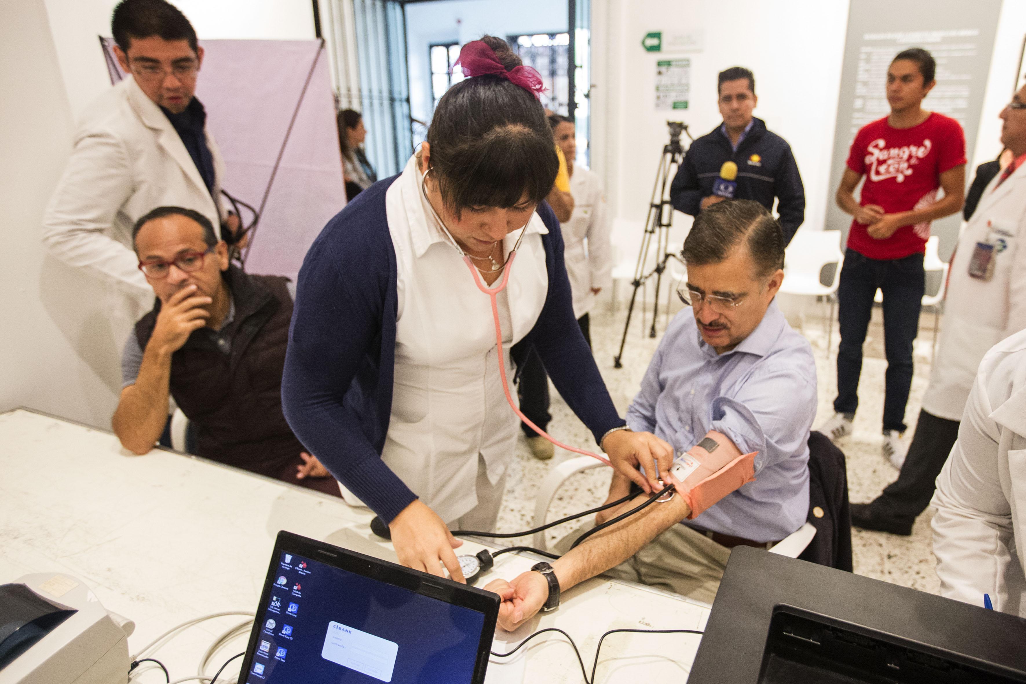 Enfermera tomando signos vitales al Rector General de la Universidad de Guadalajara (UdeG), maestro Itzcóatl Tonatiuh Bravo Padilla