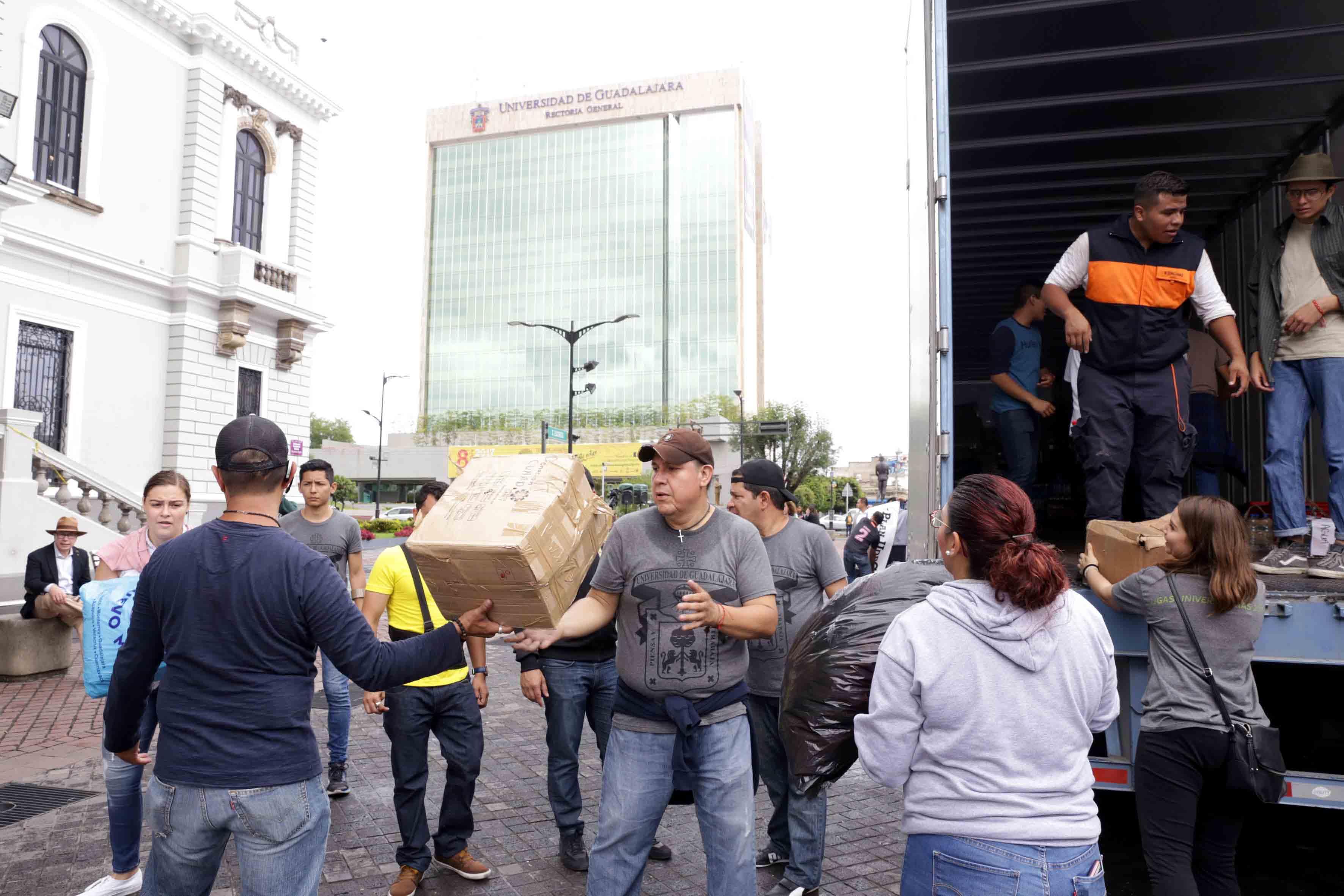 Comunidad universitaria apoyando en la carga de camión de víveres, textiles, medicamentos y artículos utilitarios.