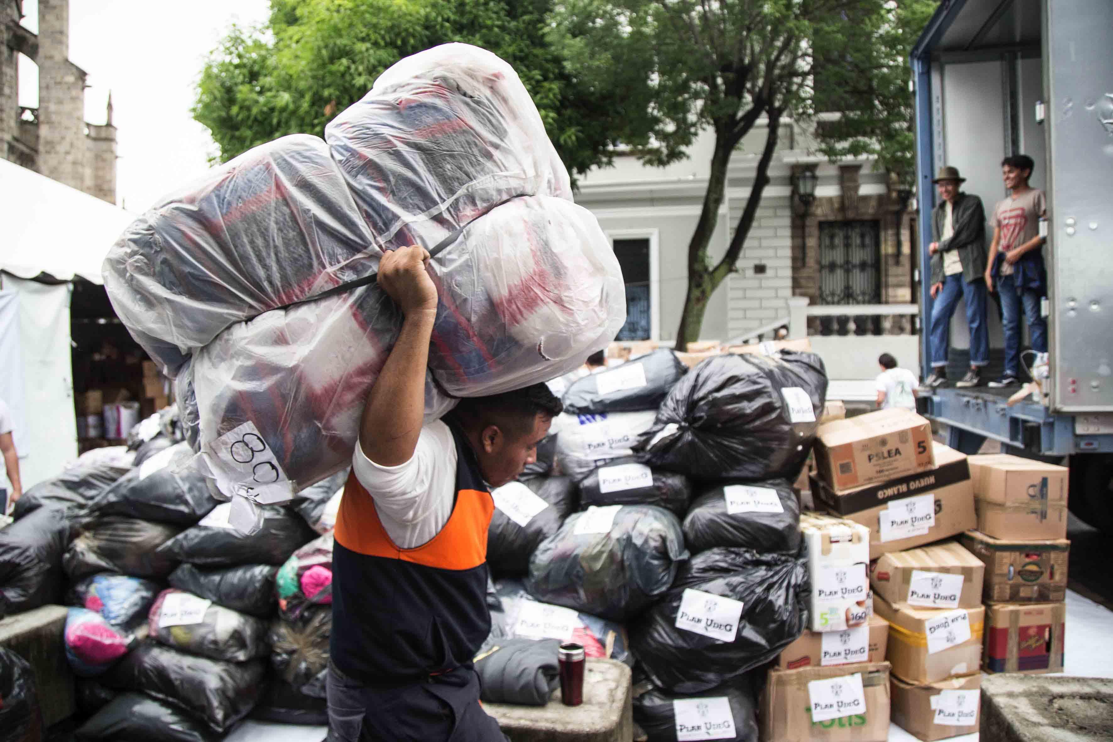 Brigadista cargando cobijas empaquetadas para la carga de caminones que irán a los damnificados.