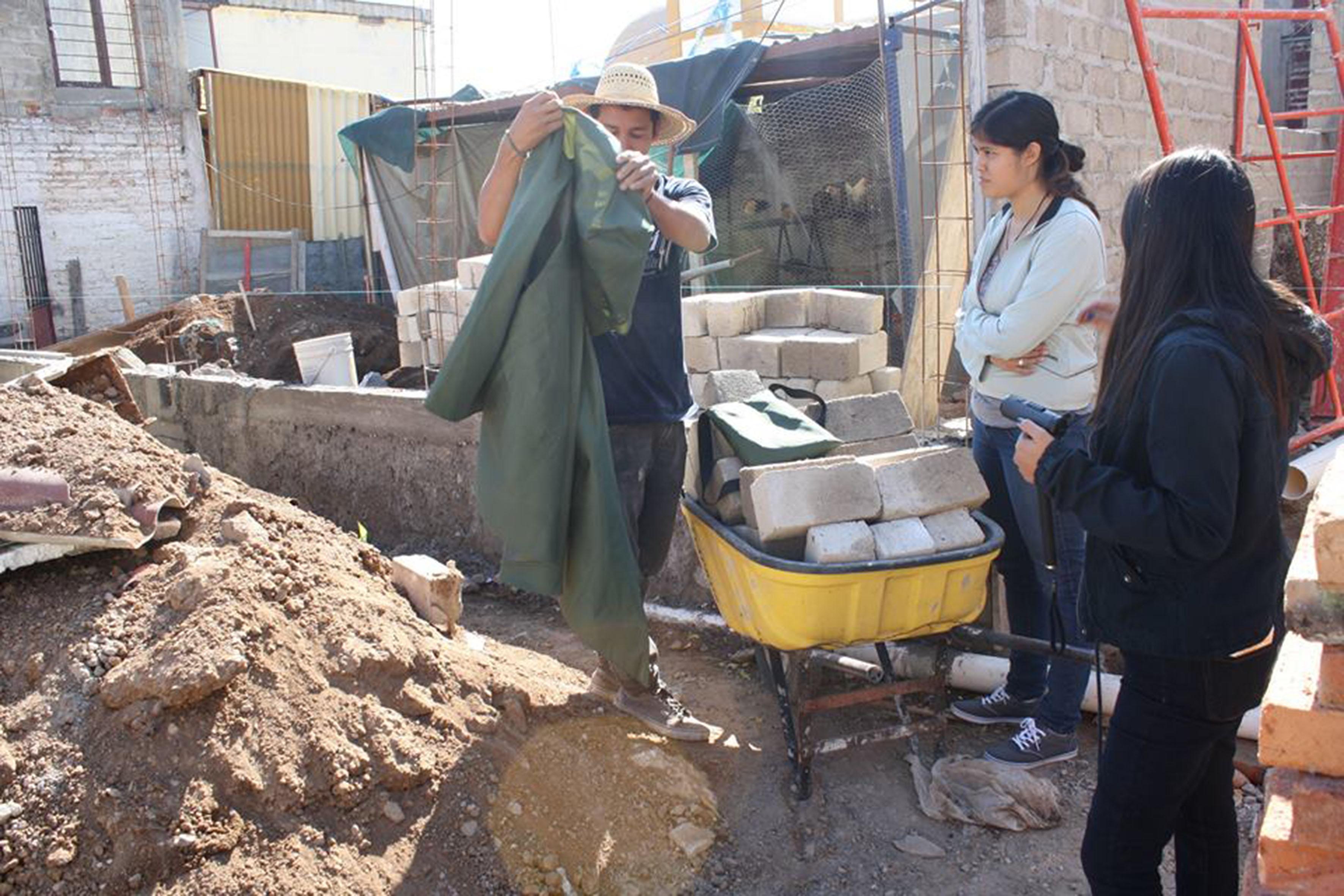 Trabajador de la construcción observando la capa kanan que le fue propocionada por estudiantes del CUAAD para probársela.