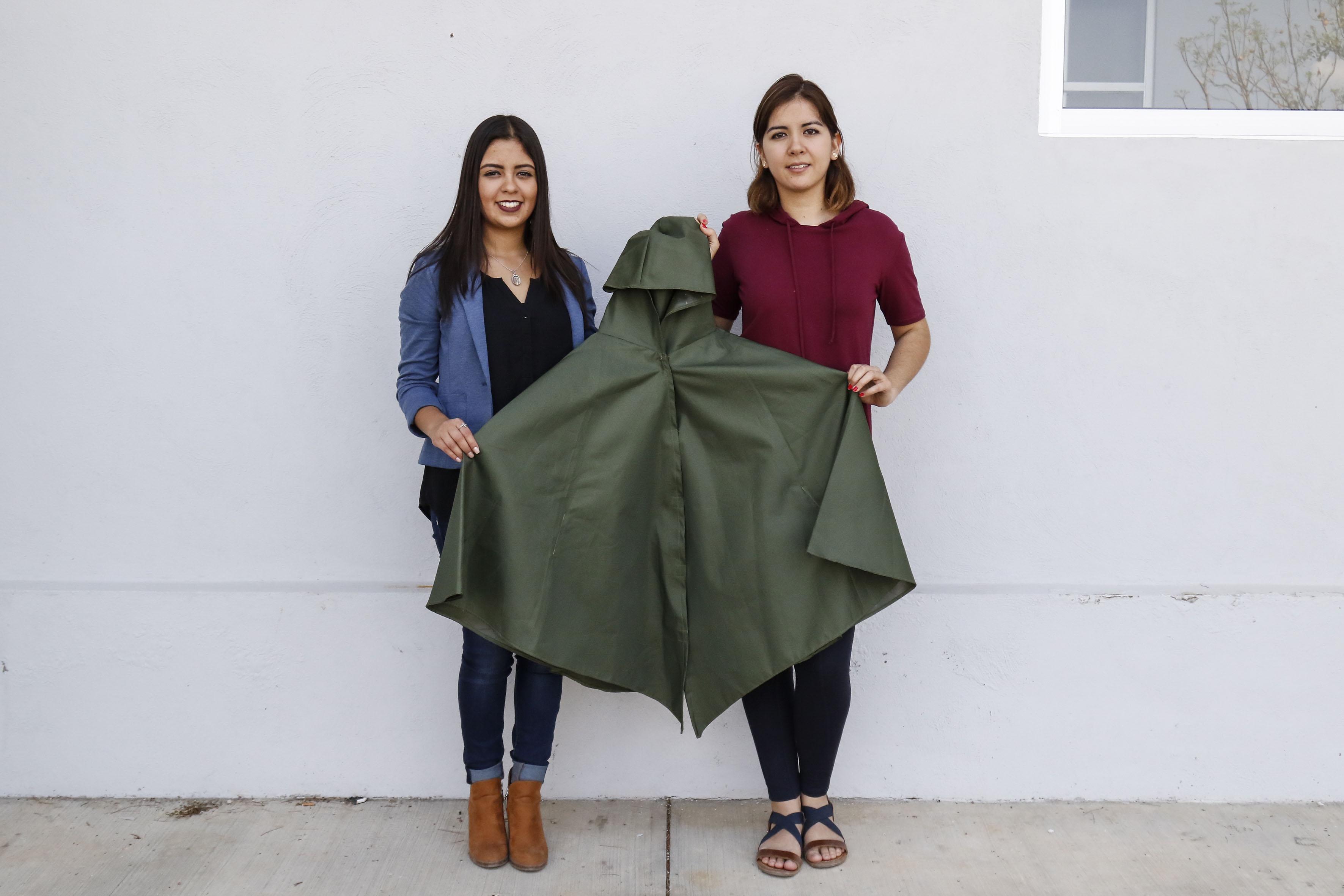 Jóvenes estudiantes de la carrera de Diseño Industrial, mostrando la capa Kanan que crearon para los migrantes y que ahora servirá para los rescatistas en los escombros.