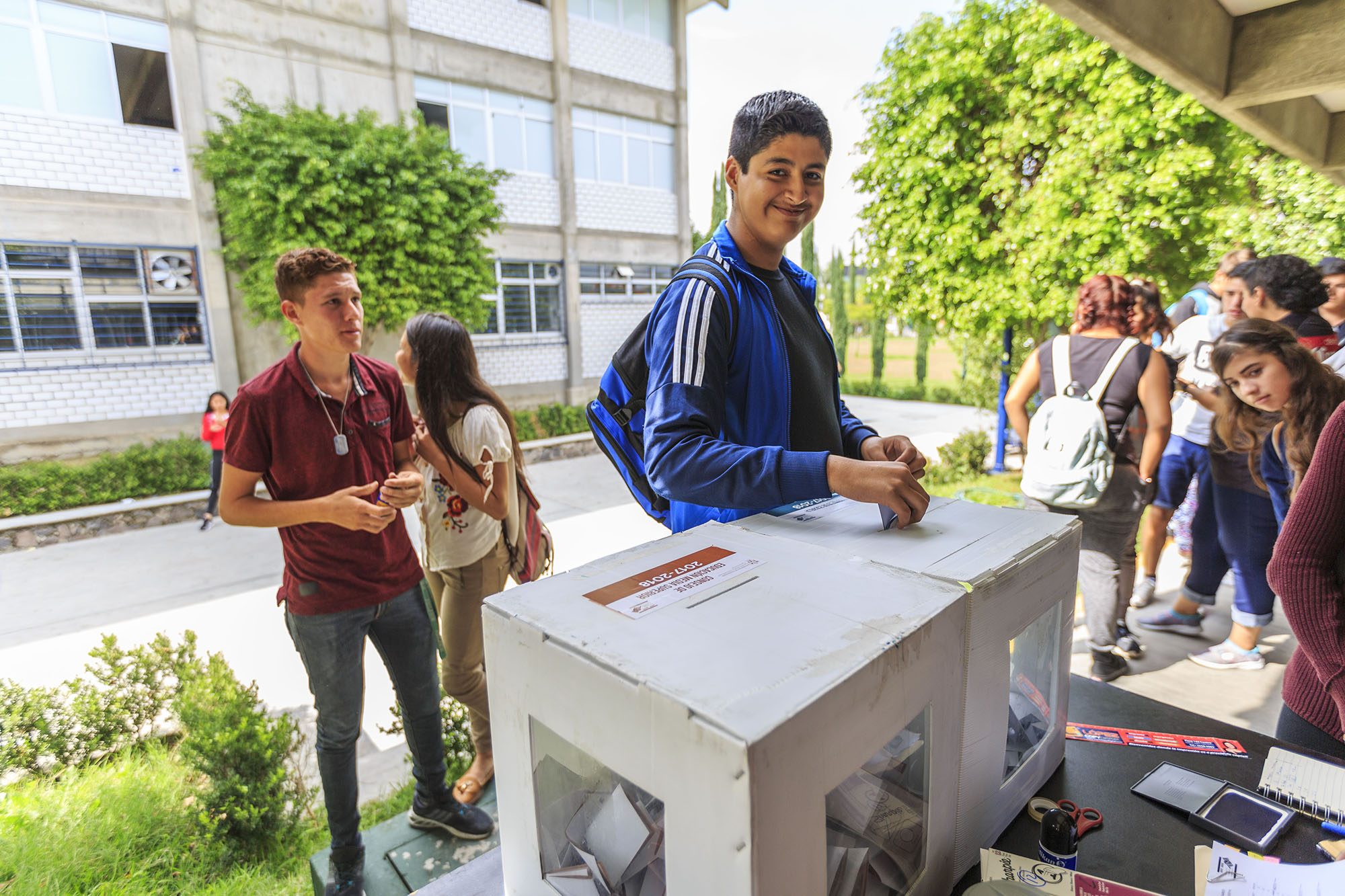 Alumnos del Sistema de Educación Media Superior de la Universidad de Guadalajara, votando en las urnas instaladas en sus respectivas escuelas para elegir a sus tres representantes del consejo de su escuela, así como al titular y suplente de quien los representará ante el Consejo Universitario de Educación Media Superior.