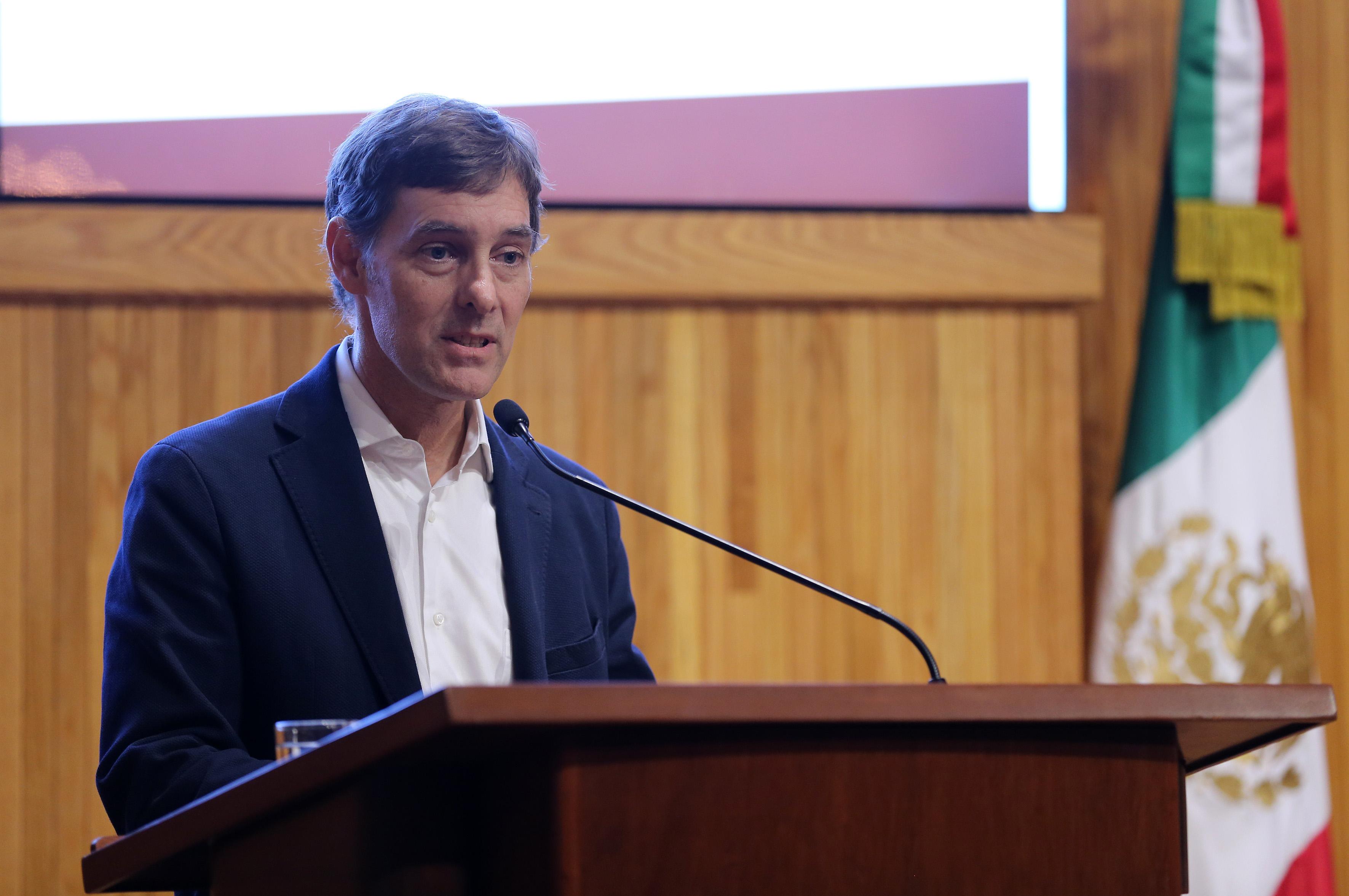 Doctor Robert Edward Curley, jefe del Departamento de Estudios Socio Urbanos del CUCSH, haciendo uso de la palabra en podium del Paraninfo para presidir la mesa de presentación de la catedrática.