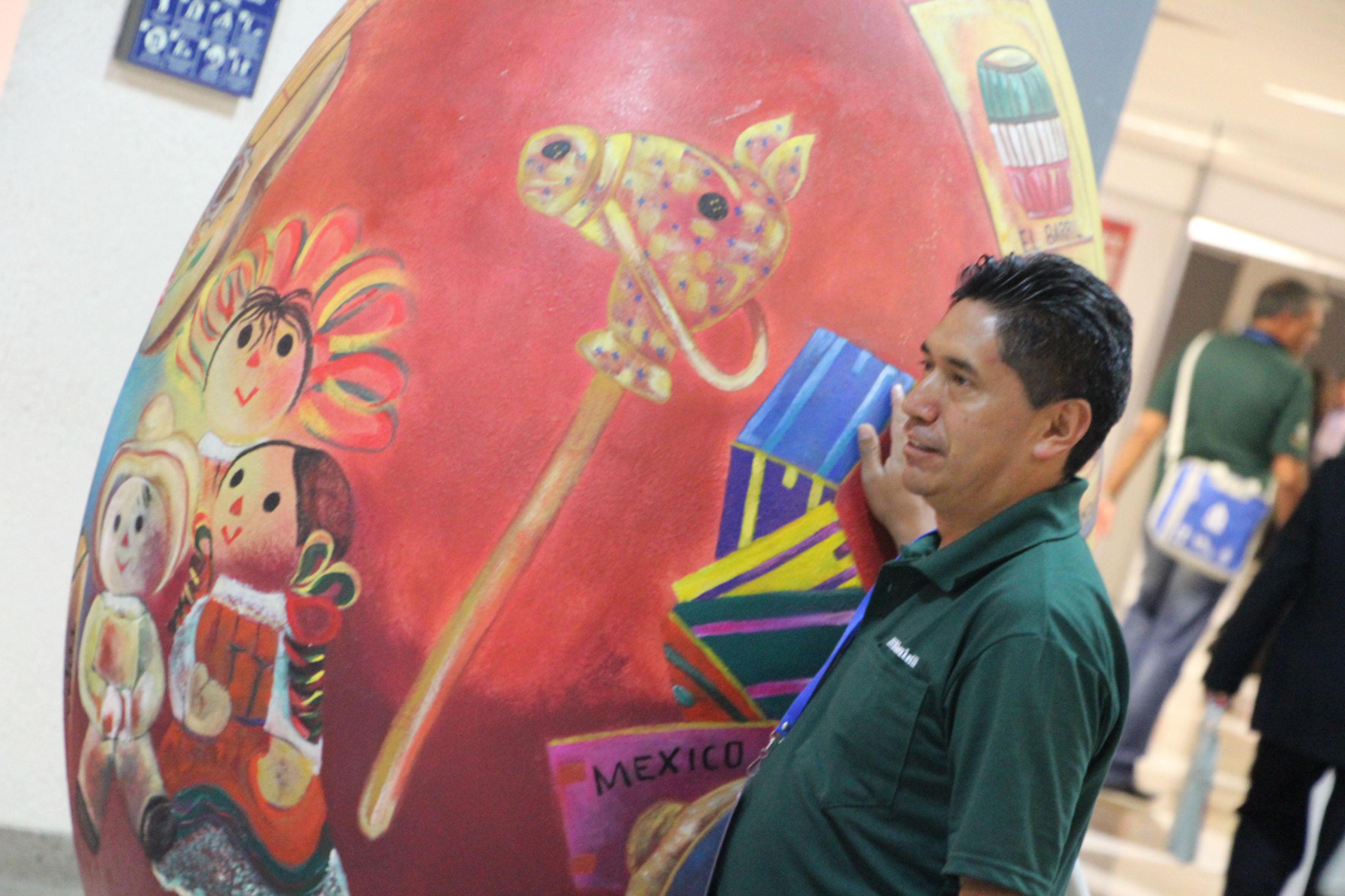 persona mostrando huevo en exhibición con paisaje de juguegos y juguetes típicos de México.