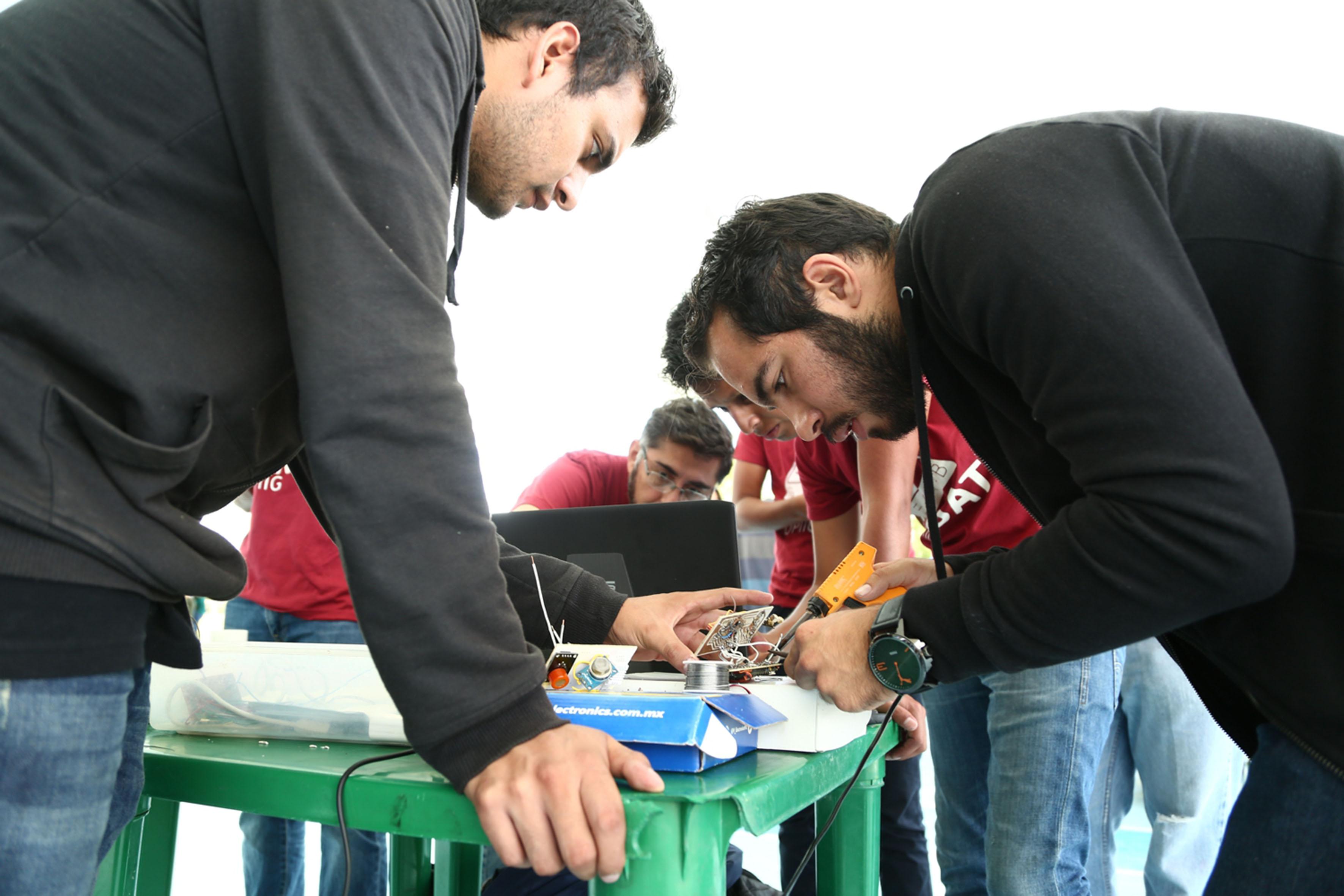 Estudiantes de ingeniería soldando con un cautín, piezas y circuitos para su satélite en miniatura.