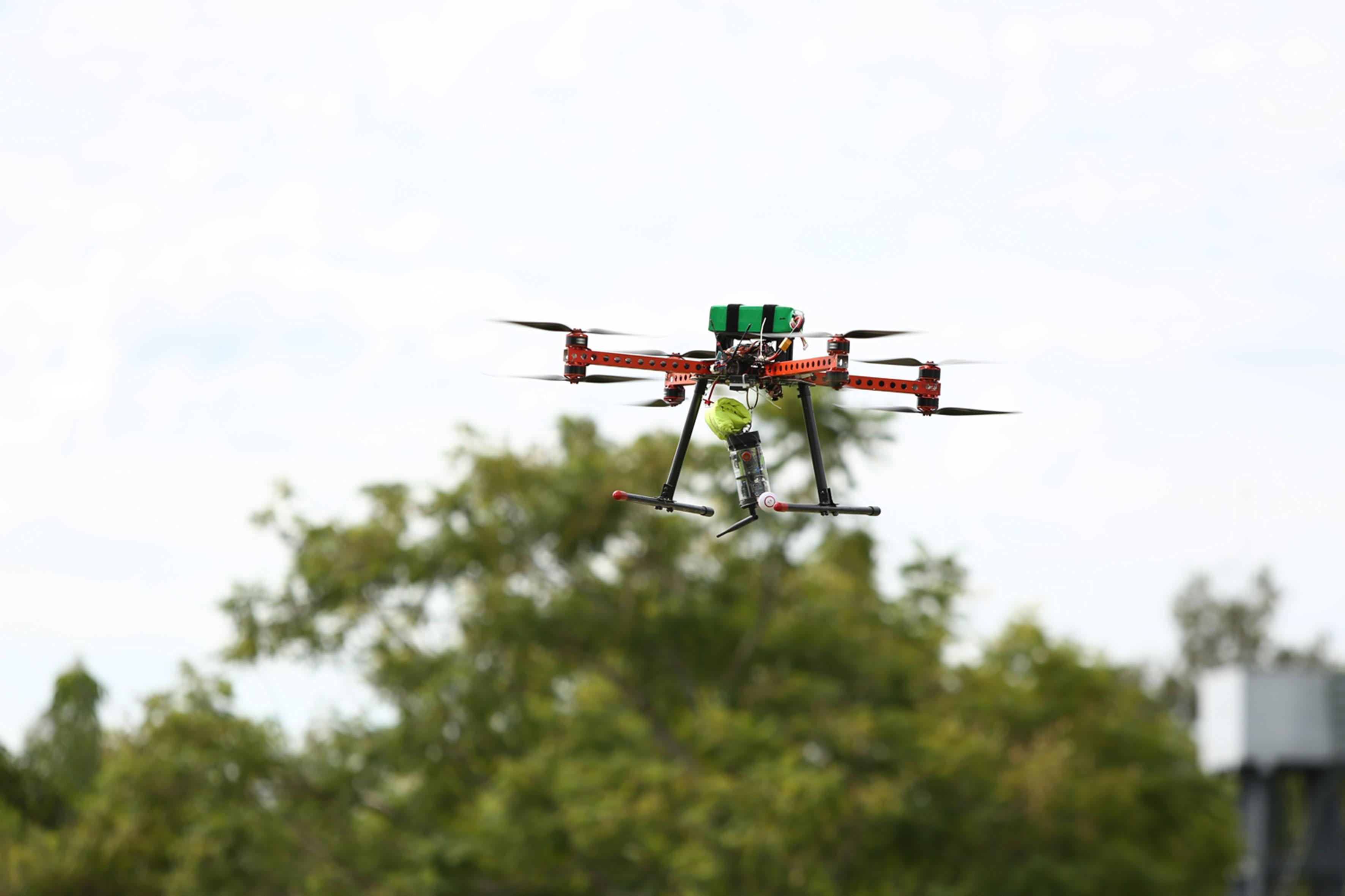 Drone volando por los aíres del centro universitario, cargando uno de los satélites en miniatura, elaborado por los estudiantes de ingienería.