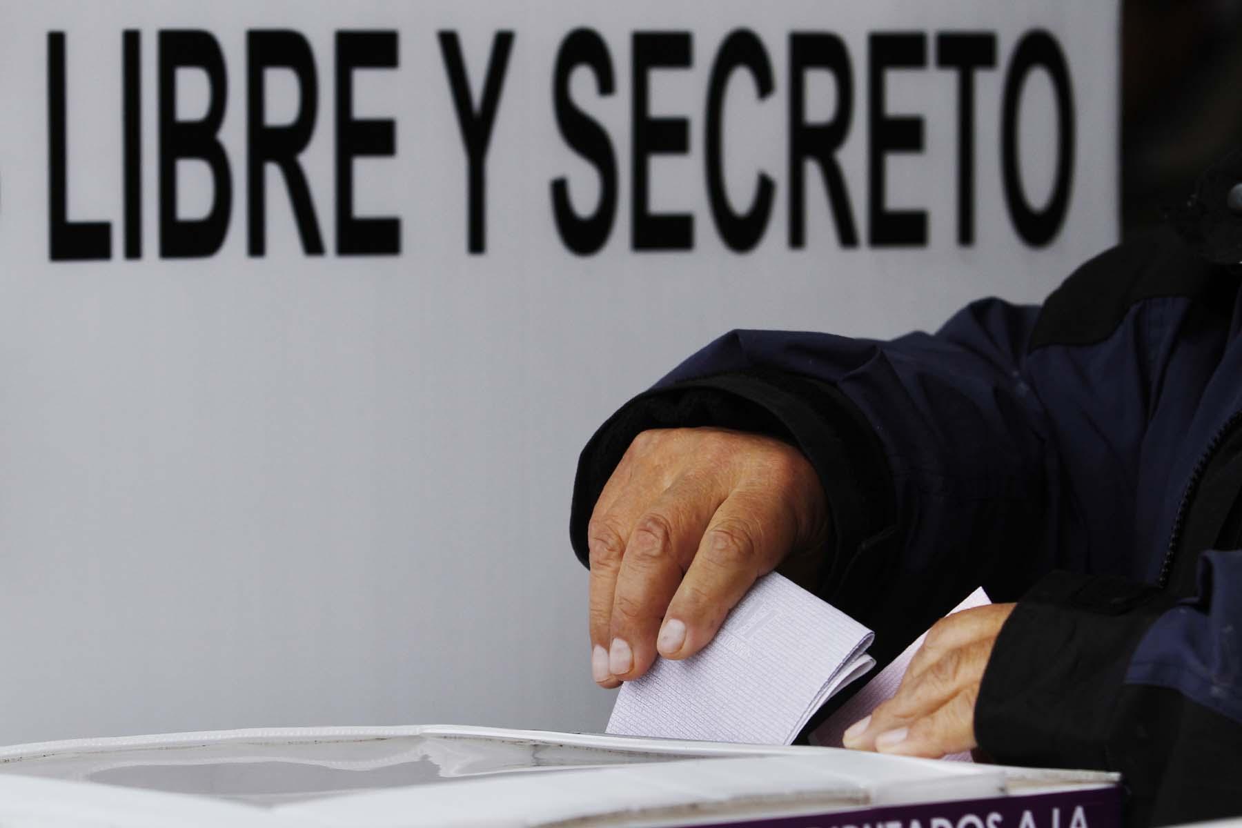 Mano de una persona depositando su voto en la urna