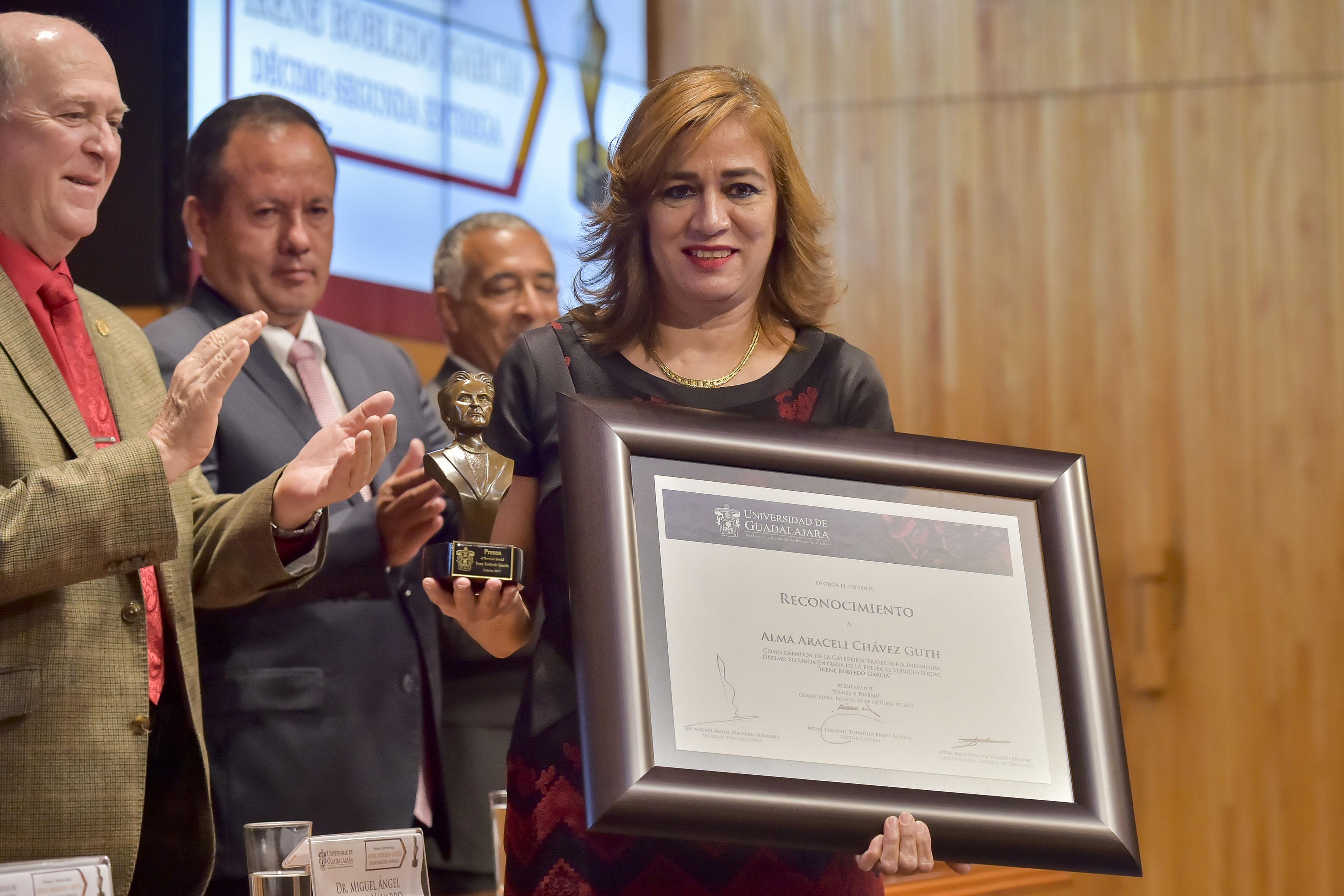 Alma Araceli Chávez Guth mostrando su diploma y presea Irene Robledo