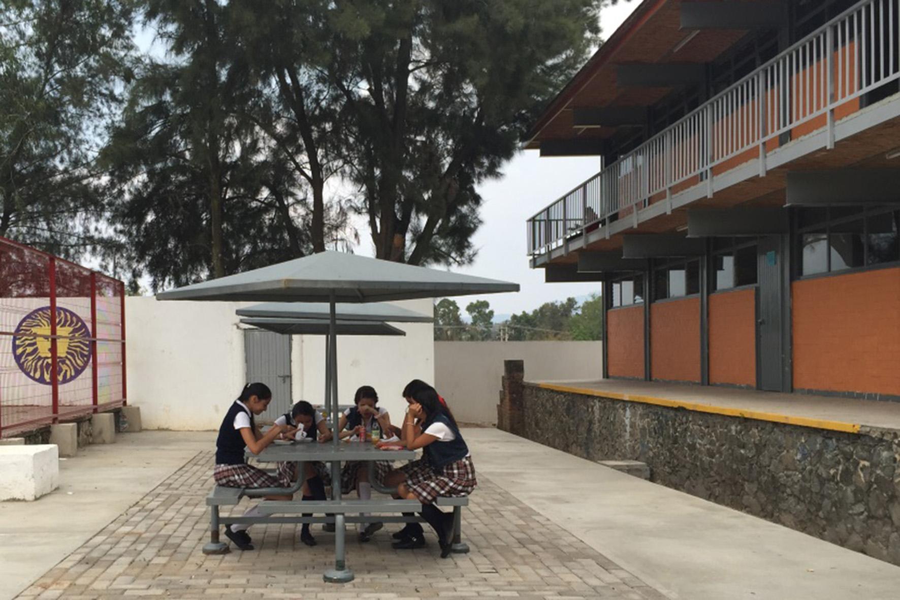 Grupo de adolescentes de preparatoria sentadas tomando un refrigerio en las zonas destinadas para descanso del módulo preparatoriano.