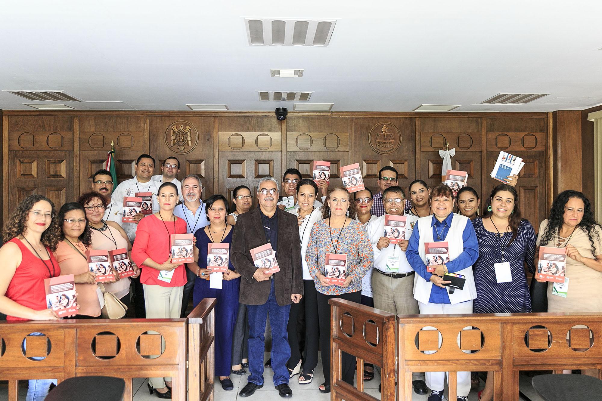 Profesores del SEMS mostrando el libro  titulado Reconstrucción de una experiencia institucional de formación de docentes en el diplomado en competencias docentes de la educación media superior