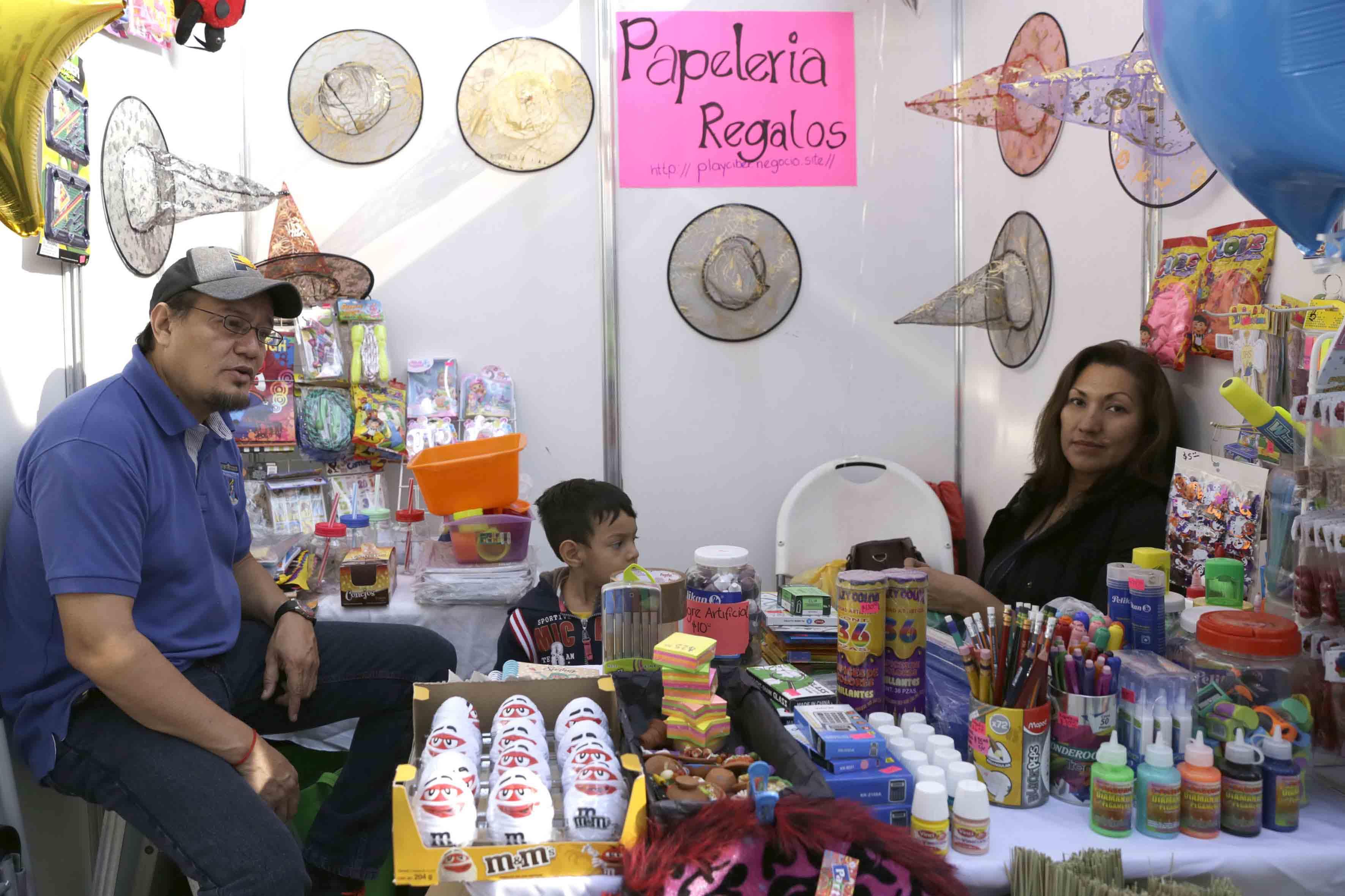 Padres de familia en su stand ofreciendo sus productos