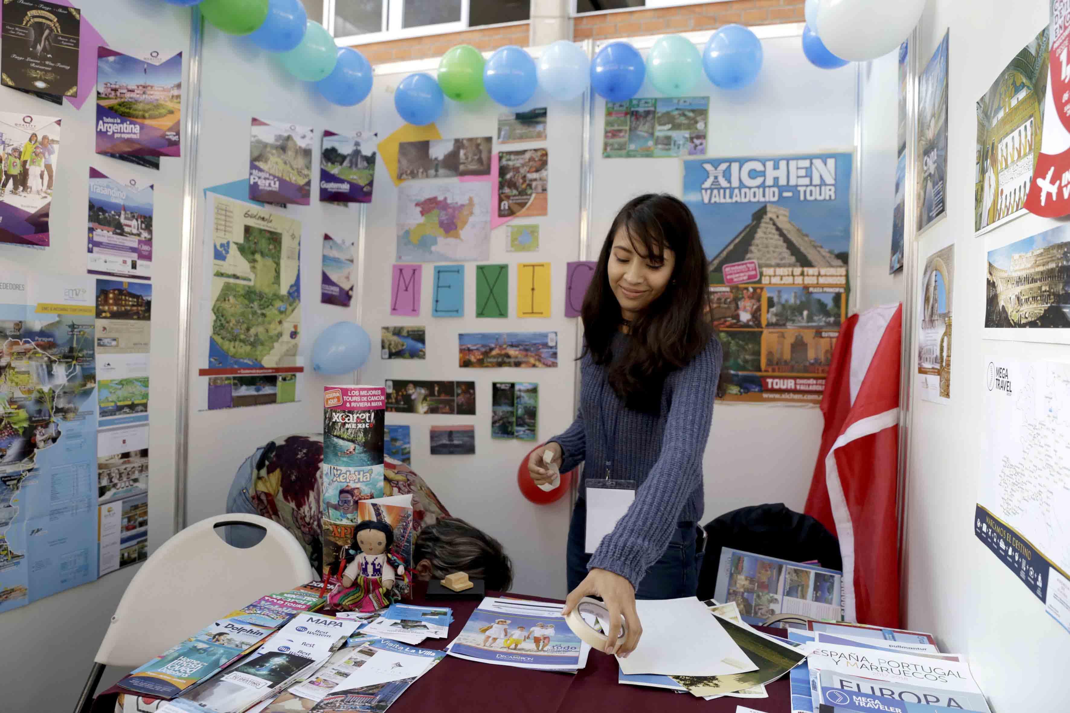 Joven en su stand mostrando sus productos
