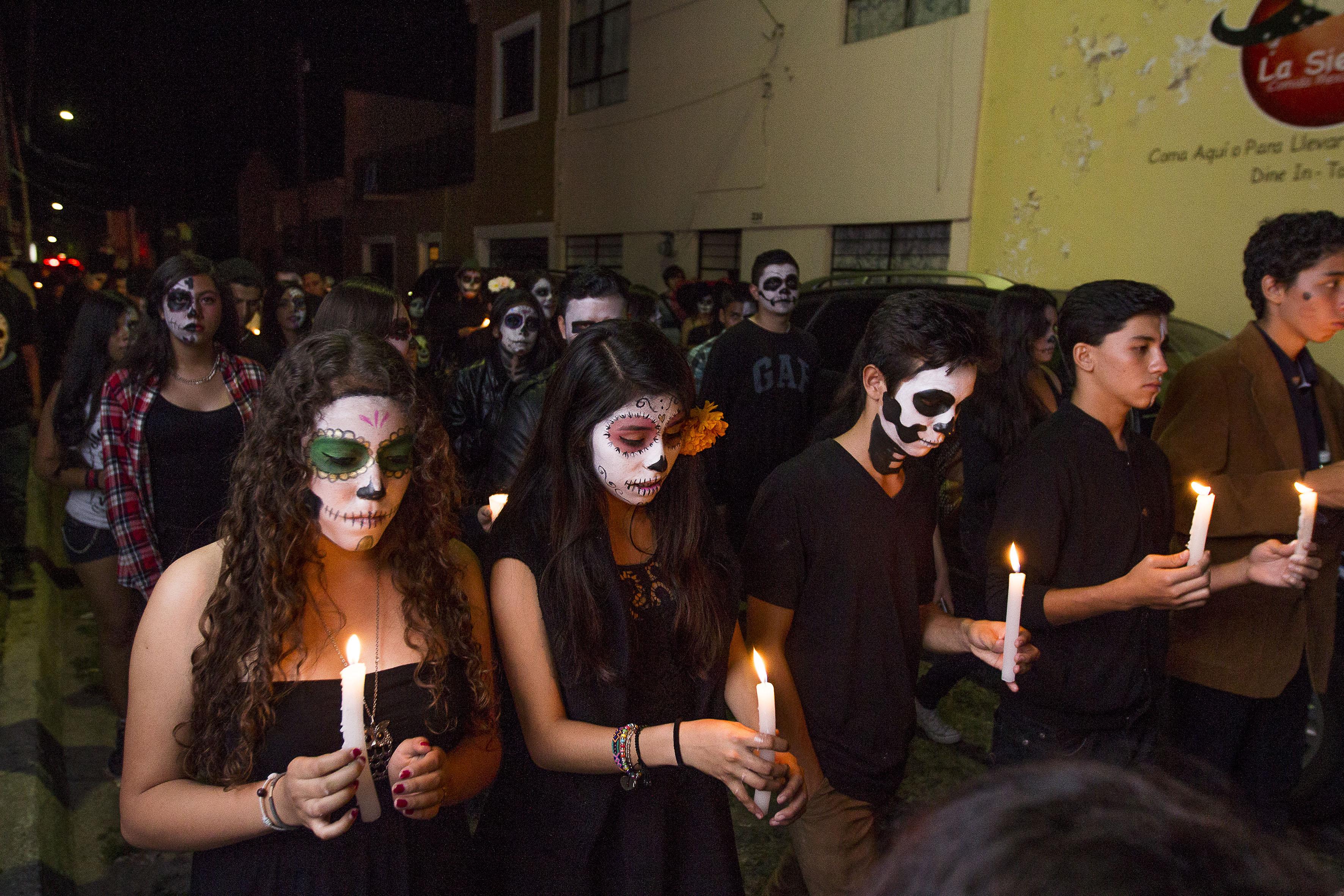 Estudiantes vestidos de catrinas caminado de noche por las calles