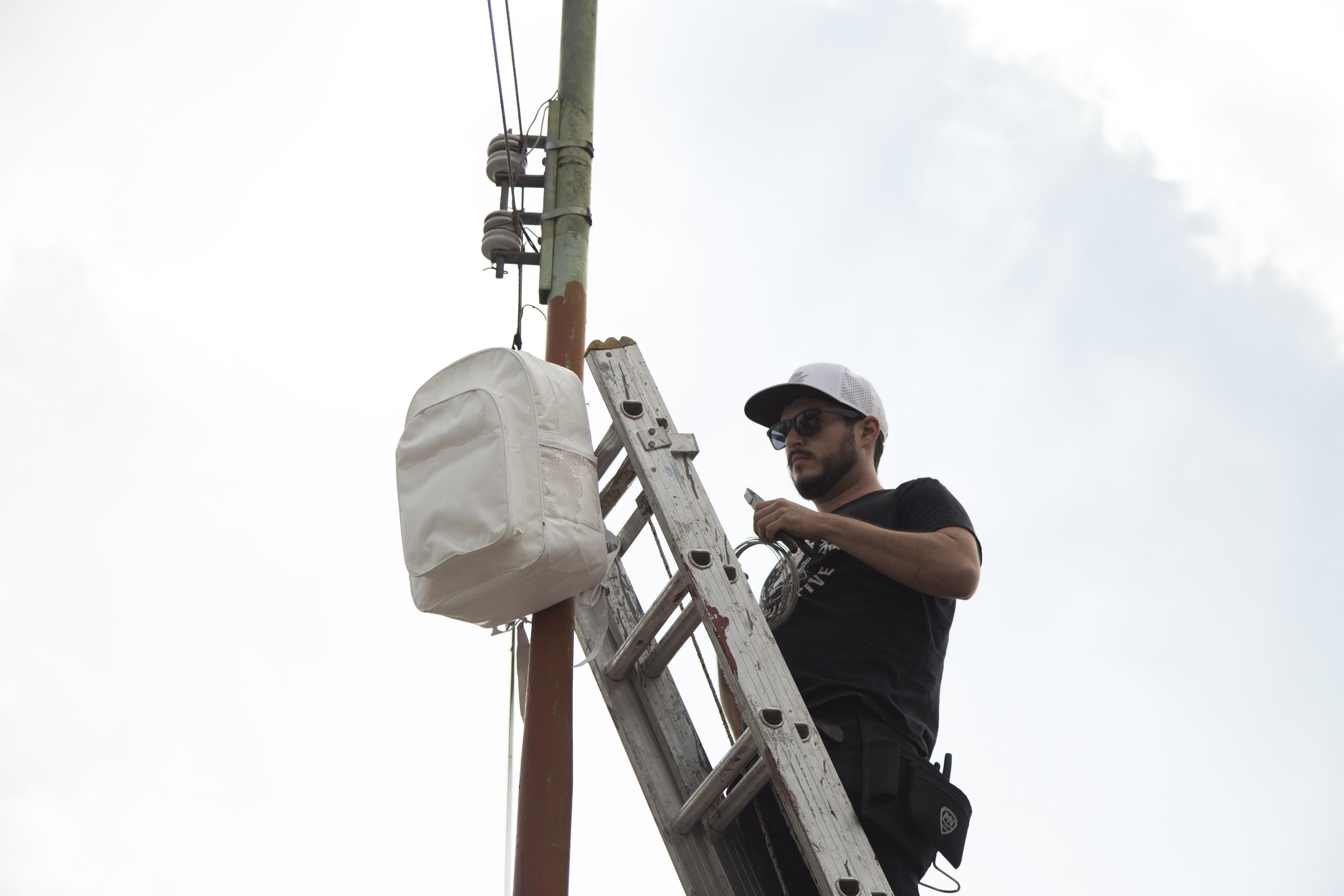 """Joven colgando mochila blanca en memoria del joven Francisco Álvarez Quezada –conocido como """"Panchito"""""""