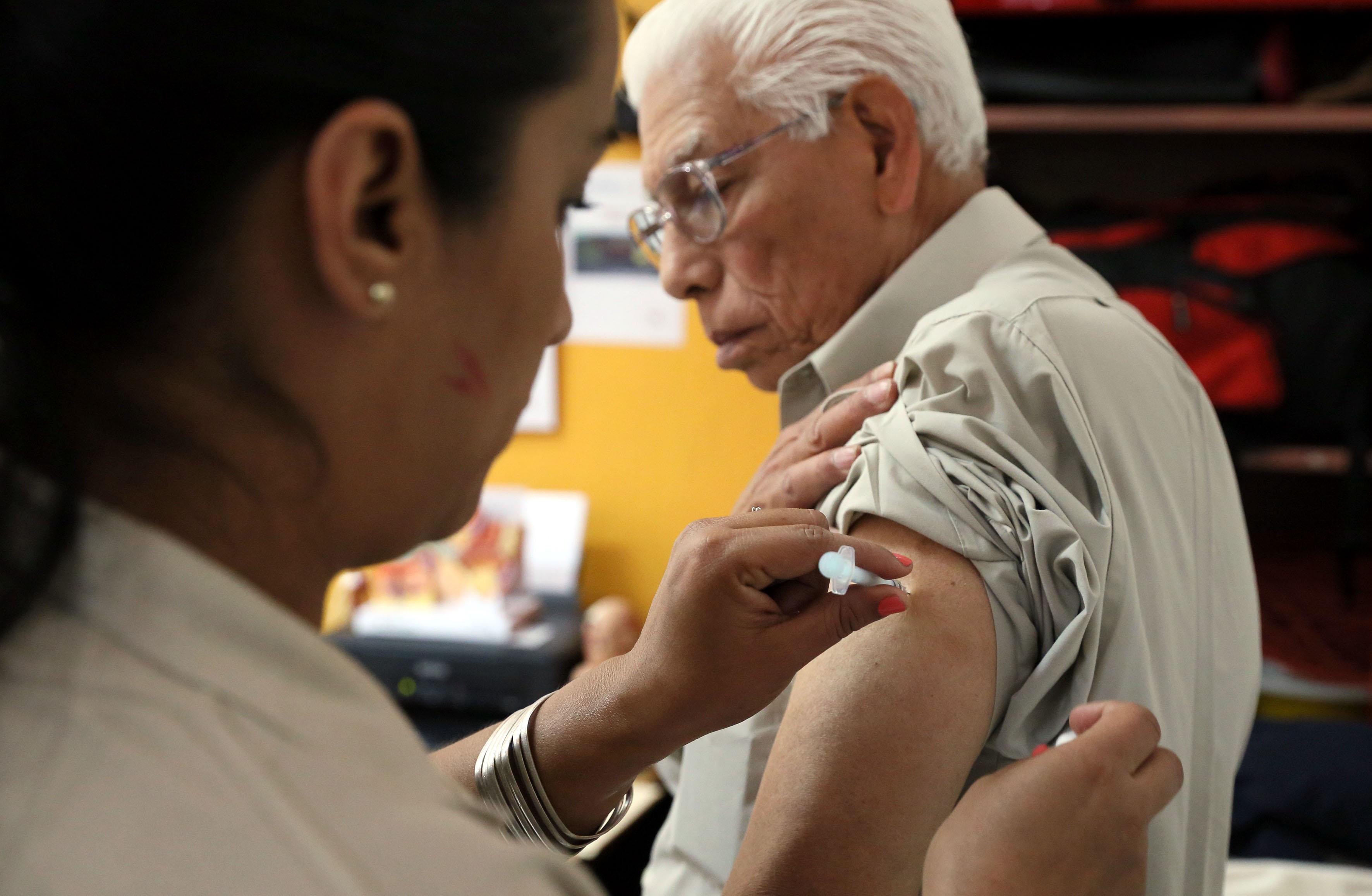 Hombre de la tercera edad, aplicándose la vacuna para prevenir la influenza.