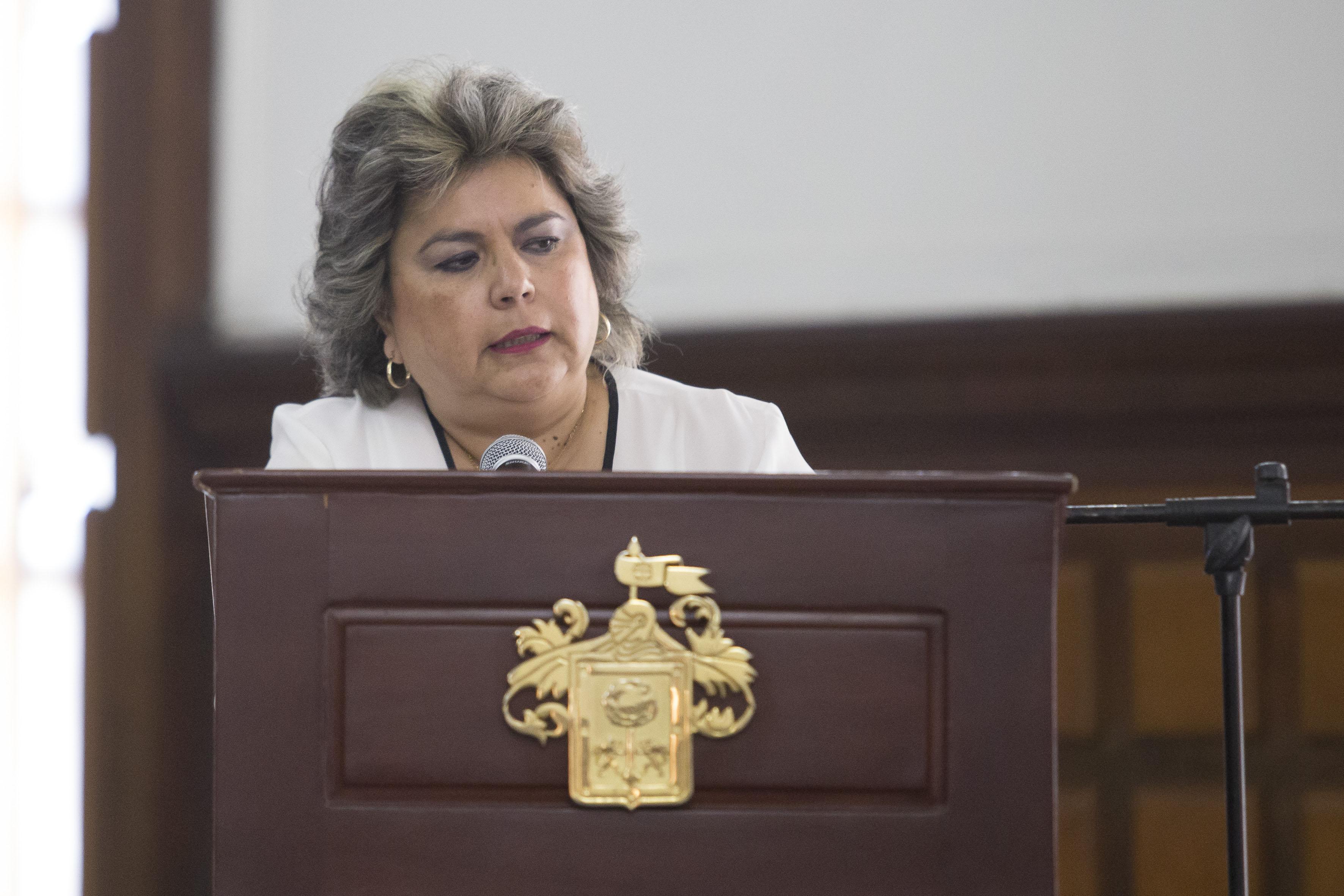 Servidora pública, participante en ceremonia de reconocimiento, haciendo uso de la palabra en podium del salón de Cabildo de Palacio Municipal.