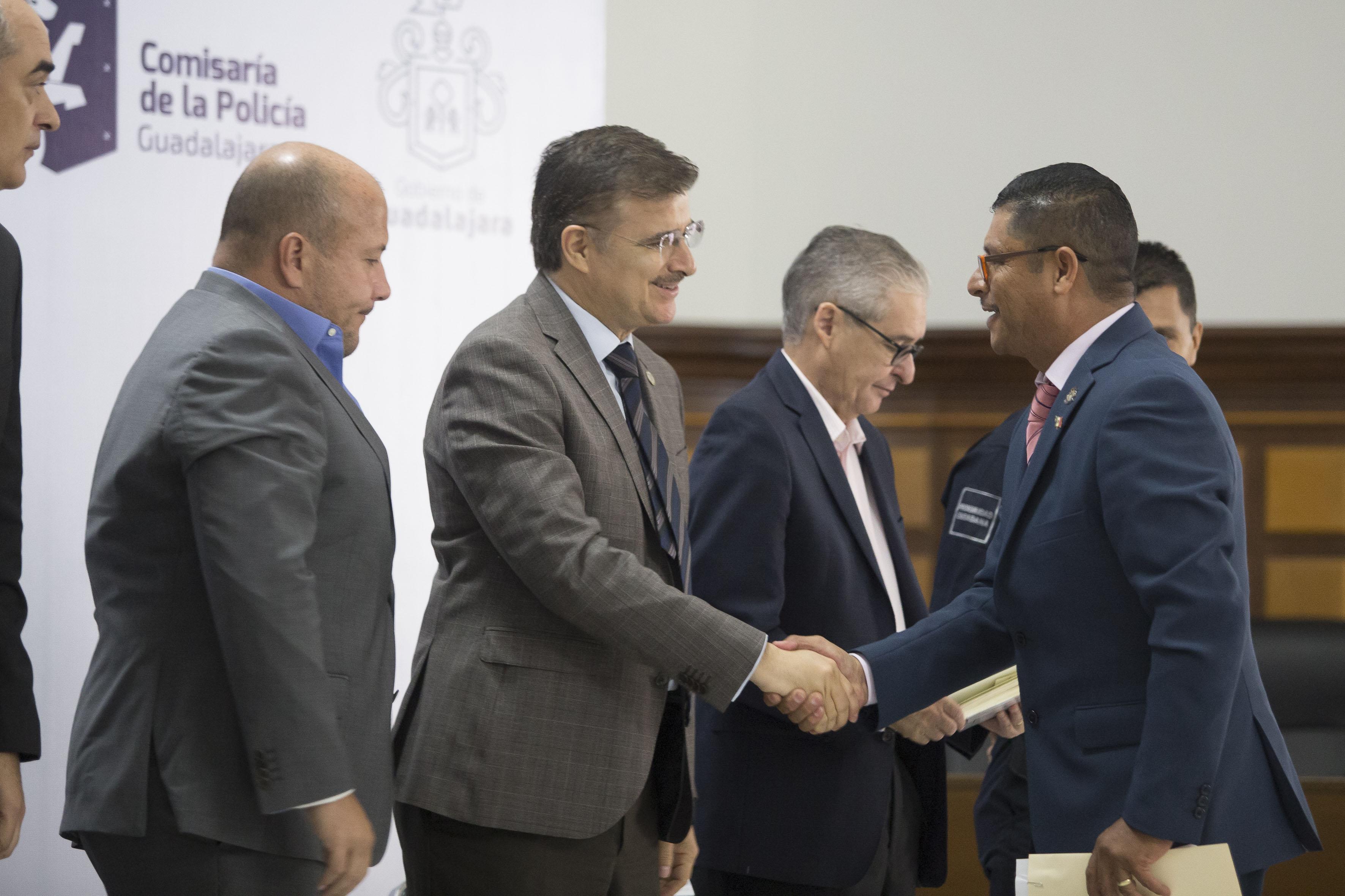 maestro Itzcóatl Tonatiuh Bravo Padilla, Rector General de la Universidad de Guadalajara, felicitando con saludo de mano al comandante José de Jesús de Anda Zambrano.