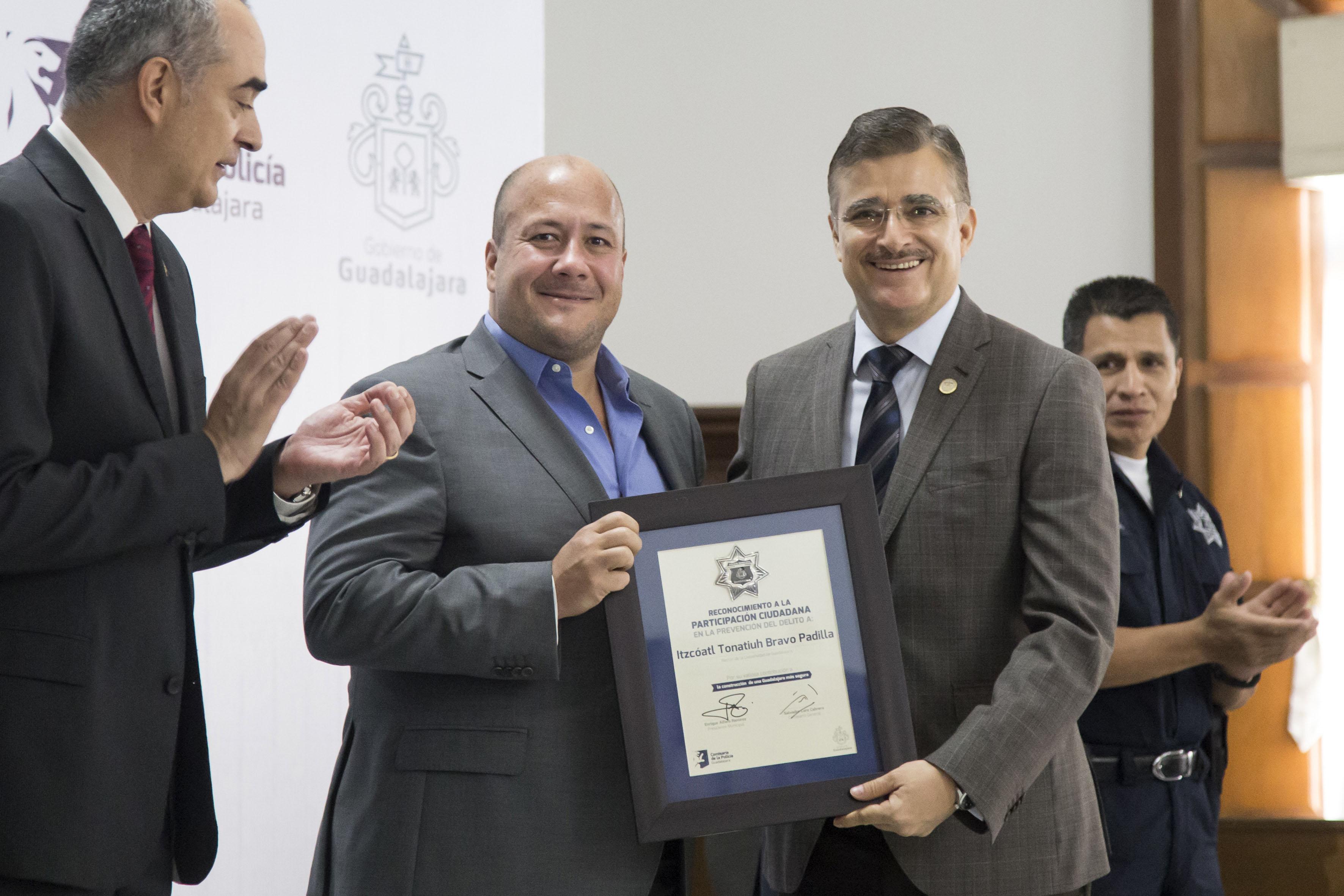 El Presidente Municipal de Guadalajara, maestro Enrique Alfaro Ramírez, entregando una placa de reconocimiento a la participación ciudadana para la prevención del delito al Rector General de la Universidad de Guadalajara, maestro Itzcóatl Tonatiuh Bravo Padilla.