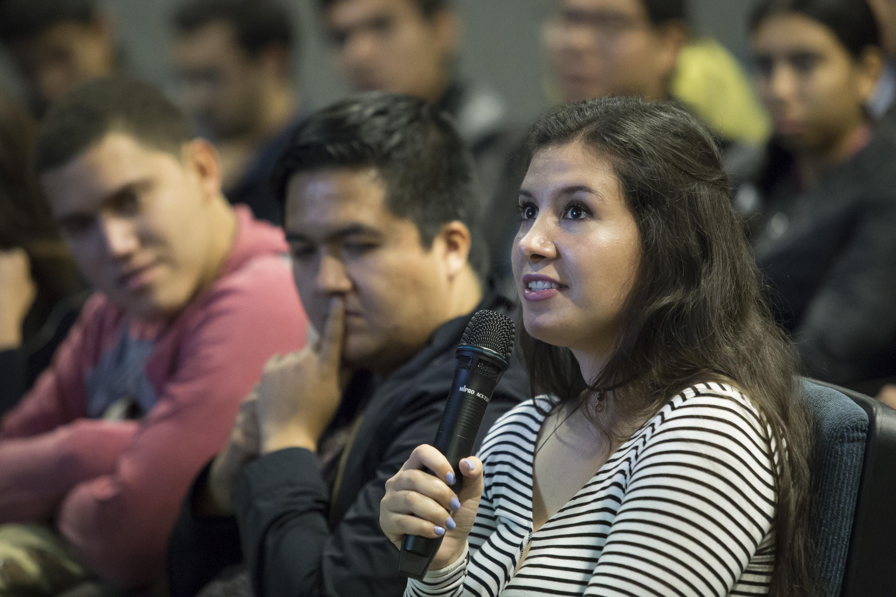 Jóven mujer estudiante, asistente a conferencia y con micrófono en mano, haciendo uso de la palabra.