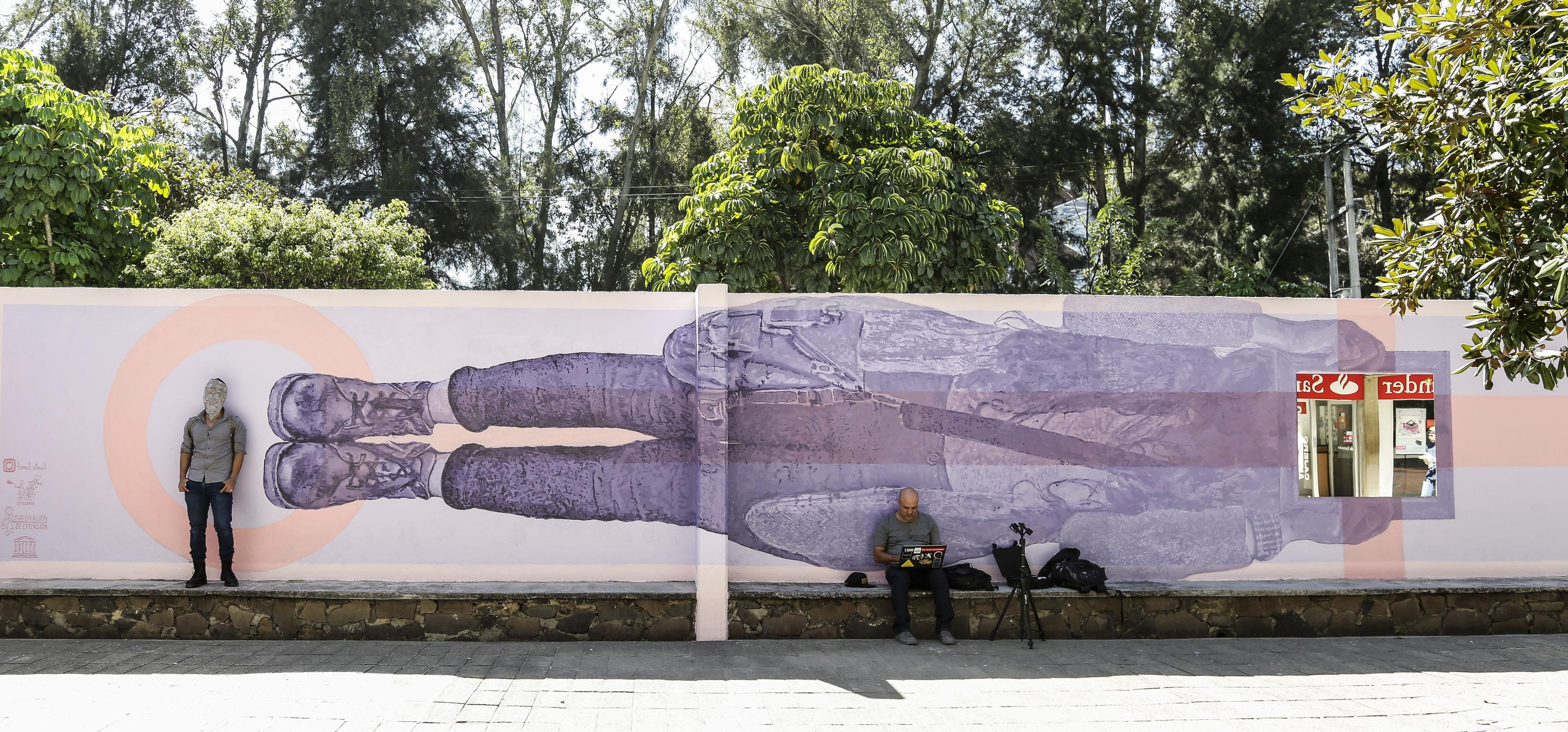 Artista urbano Himed, posando junto a su mural