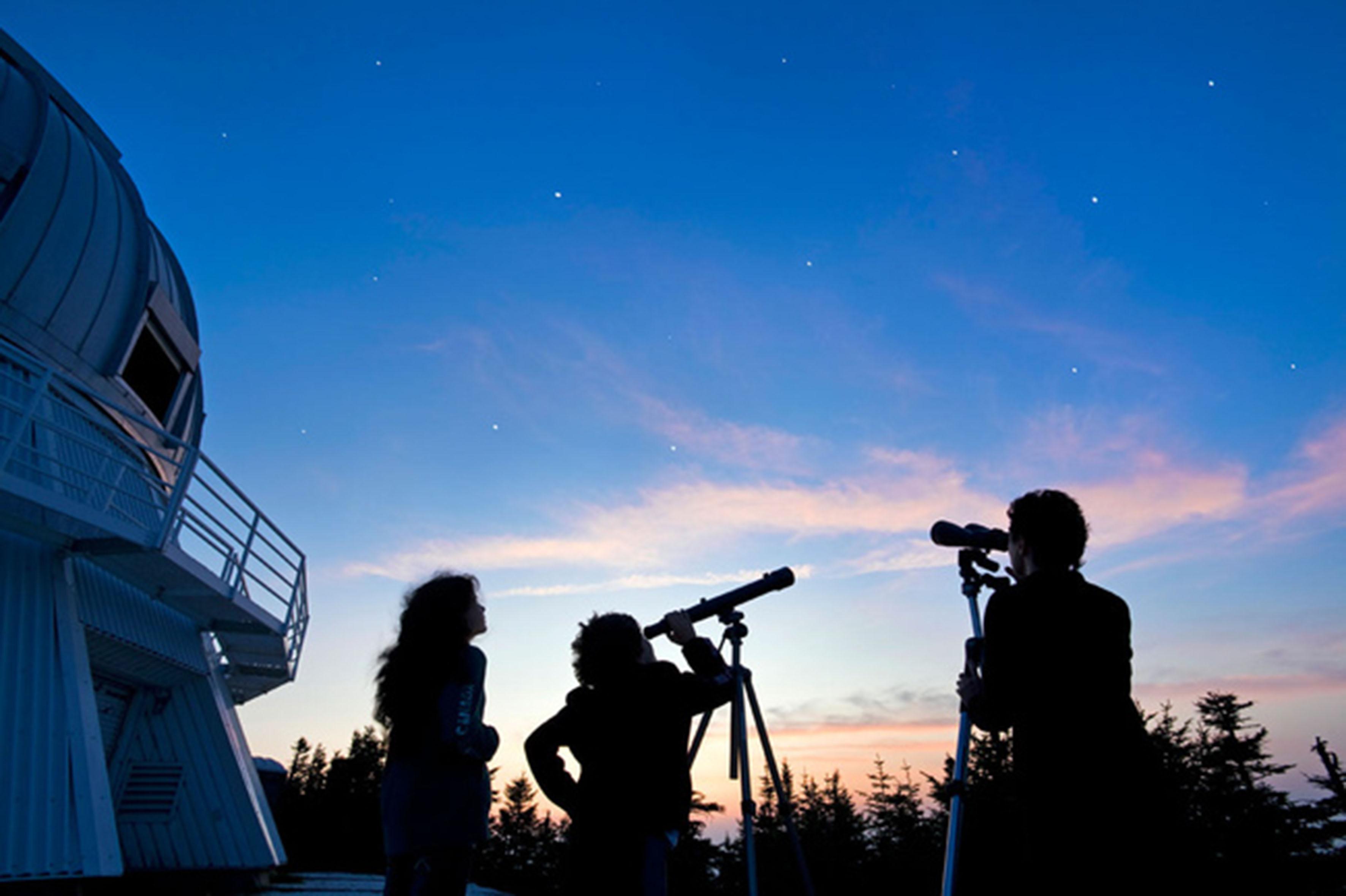 Mujeres observando al cielo a través de un telescopio