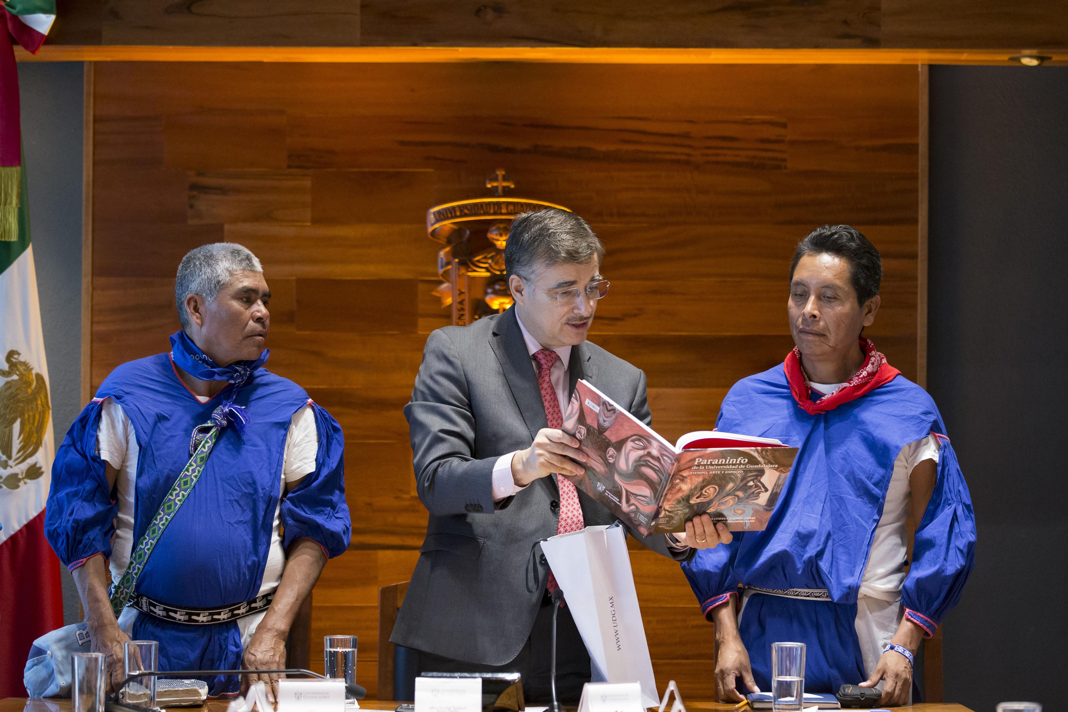 Rector General de la UdeG, maestro Itzcóatl Tonatiuh Bravo Padilla, regalando el libro del Paraninfo de la Universidad de Guadalajara a miembros de la comunidad Santa Catarina Cuexcomatitlán, del Municipio de Mezquitic, Jalisco, en firma de convenio