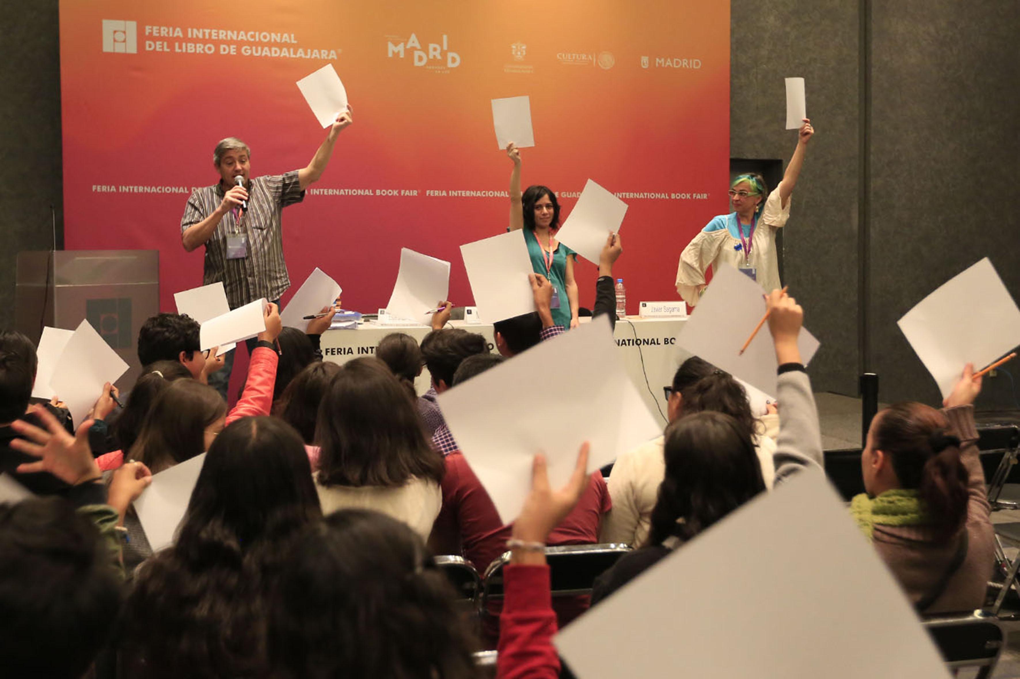 Durante conferencia 3 personas al frente levantan una hoja blanca de papel y la audiencia también lo hace