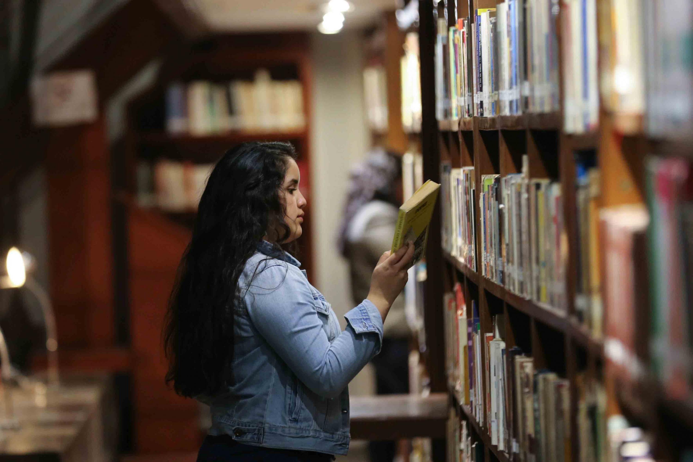 """Usuaria de la Biblioteca  Iberoamericana """"Octavio Paz"""" consultando libro de interes"""