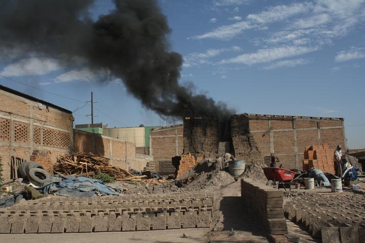 Fabrica de ladrillos arrojando humo por la incineración de los mismos.