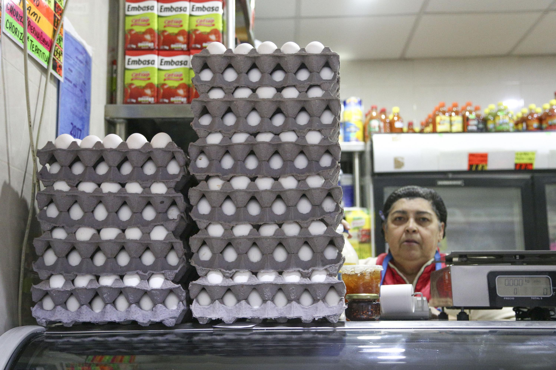 Persona laborando en una cremeria, siendo el huevo una de sus principales ventas.