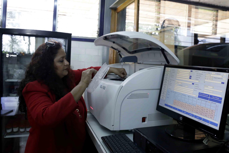 Investigadora de la Universidad de Guadalajara, utilizando la centrifugadora de laboratorio, del Centro Universitario de Ciencias de la Salud (CUCS).