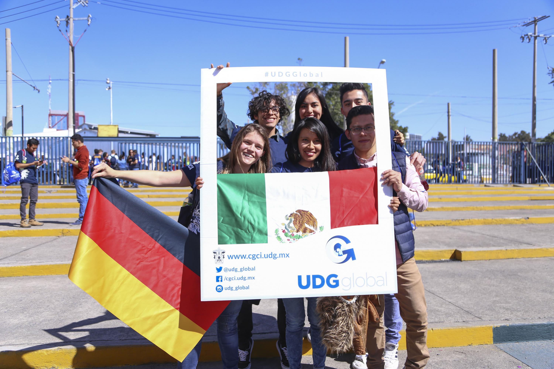 Estudiantes de intercambio tomándose fotografías con el marco de bienvenida.