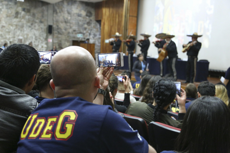 Estudiante de intercambio tomando vídeo del mariachi  que tocó durante la ceremonia de bienvenida.