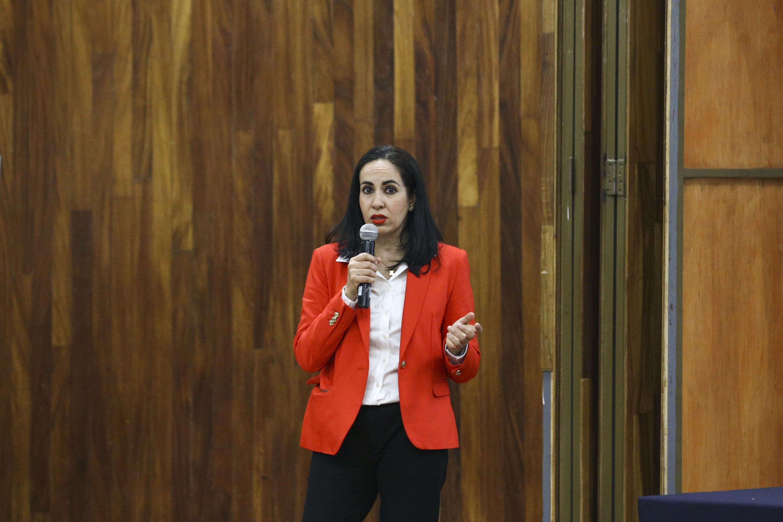 Jefa de la Unidad de Servicios Migratorios, maestra Luz Elena Argote Michel, con micrófono en mano haciendo uso de la voz.