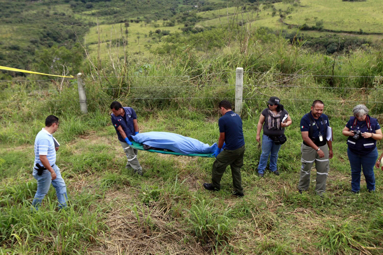 Especialistas en Ciencias Forenses, recogiendo un cuerpo en la escena del crimen.