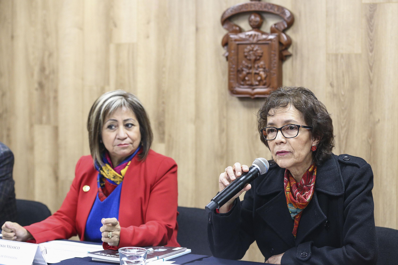 Doctora Miram del Carmen Cárdenas Torres,  titular de la Coordinación General de Extensión, maestra Rosa Eugenia Velazco Briones, titular de la Unidad de Inclusión, con micrófono en mano, haciendo uso de la palabra.