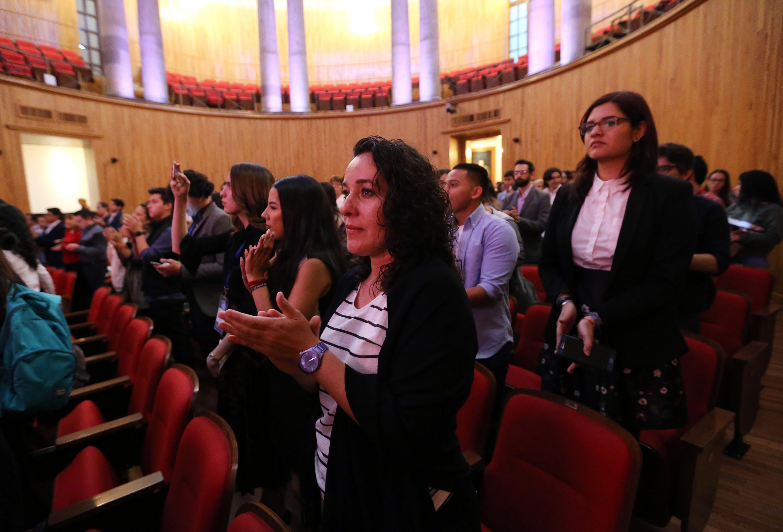 Asistentes a la conferencia aplaudiendo de pie desde su lugar