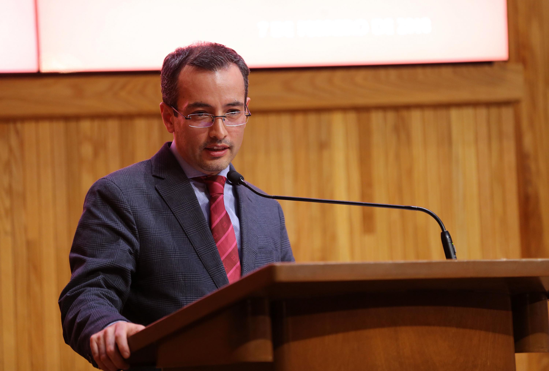 El doctor Moreno al micrófono del podium inaugurando la conferencia