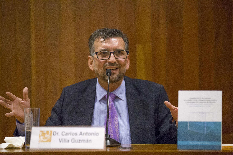 El doctor es autor del libro hablando durante la presentación en la mesa de presidium