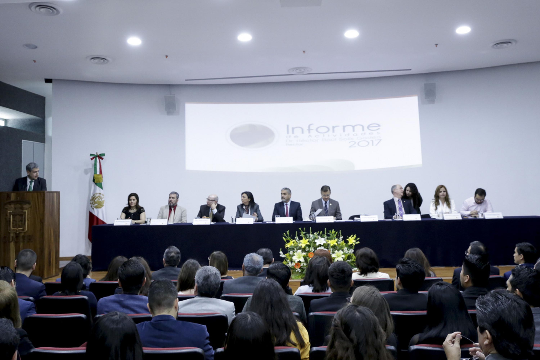 El doctor Solís Gadea hablando desde el podium dirigiendose a los 9  integrantes del presidium