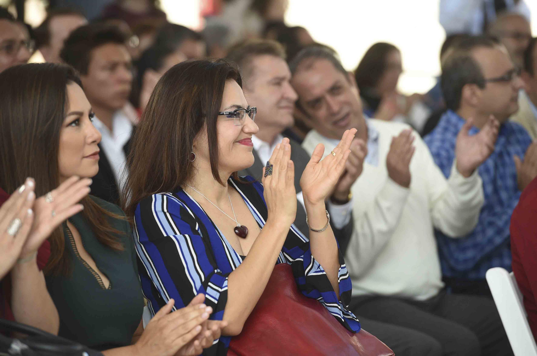 La maestra Rosas aplaudiendo durante la presentación del informe