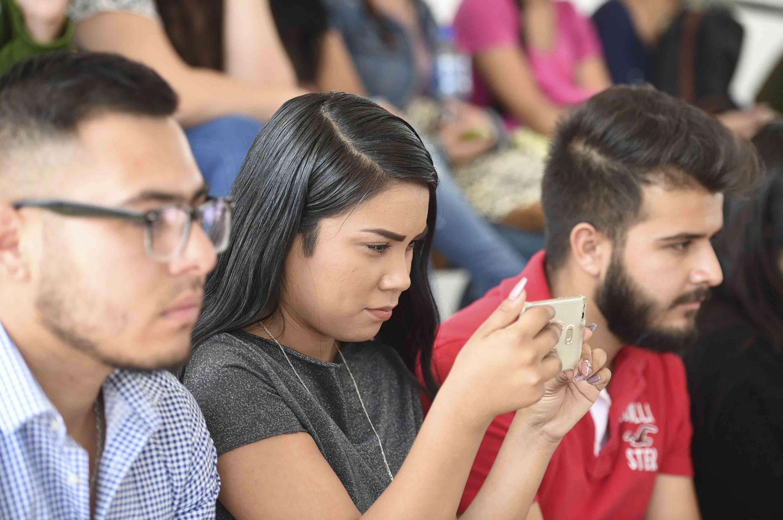 Alumna del CUTonalá mirando fijamente su telefono inteligente durante el informe
